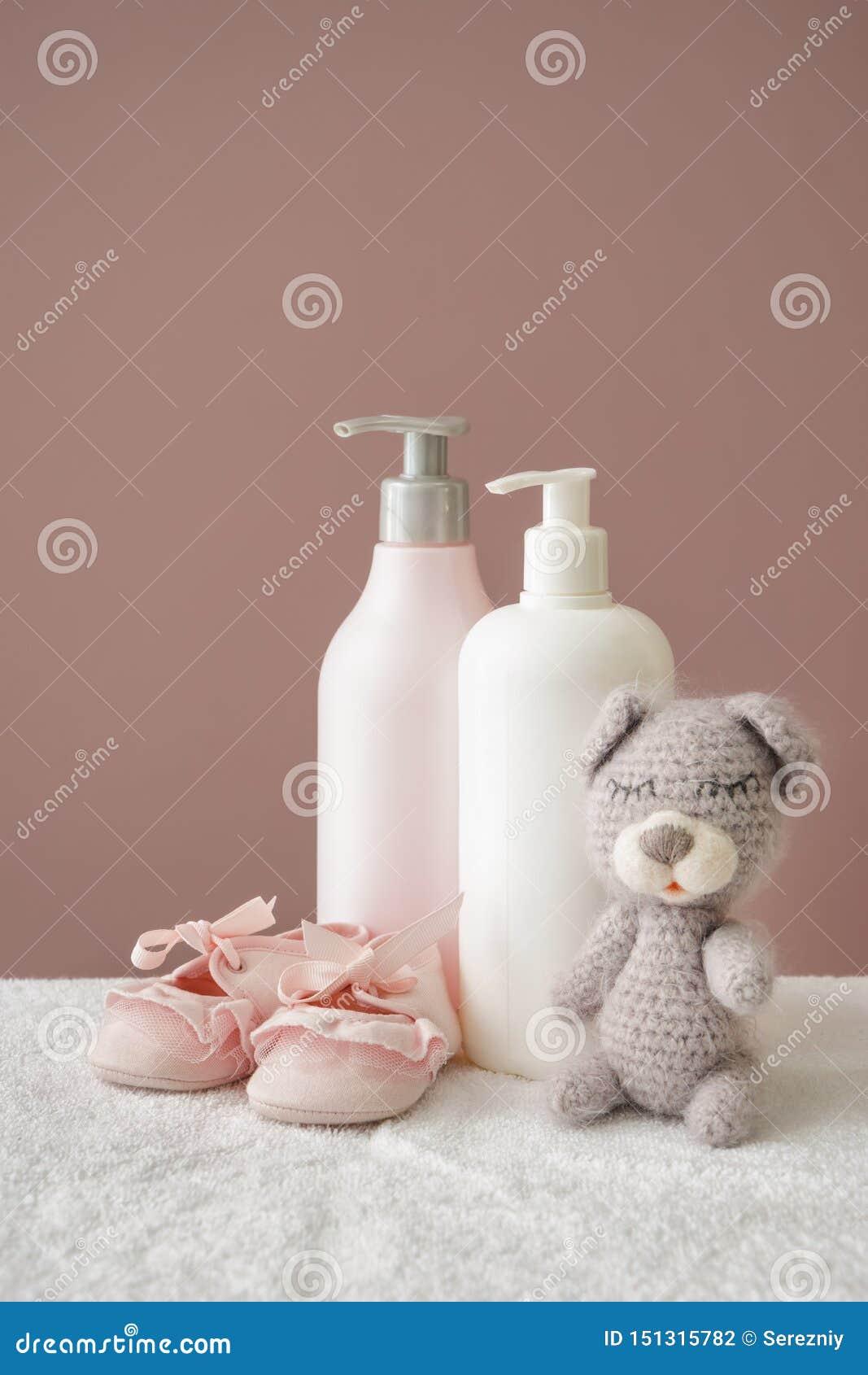 Oso de peluche con los zapatos y los cosméticos para el bebé en la toalla suave contra fondo del color