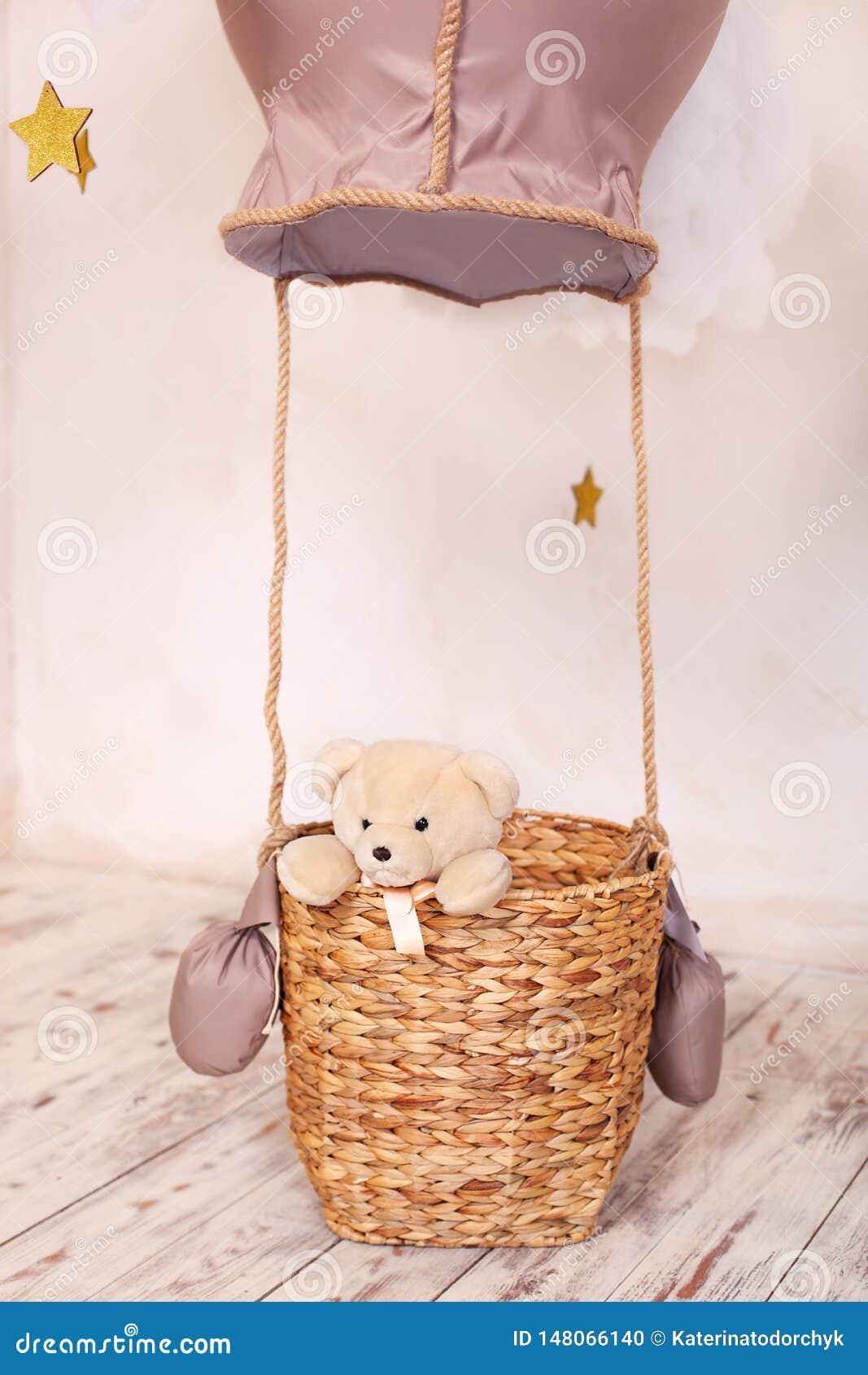 Oso de peluche que se sienta en la cesta del globo, aerostato La ubicación de los niños para una sesión fotográfica: un globo y n