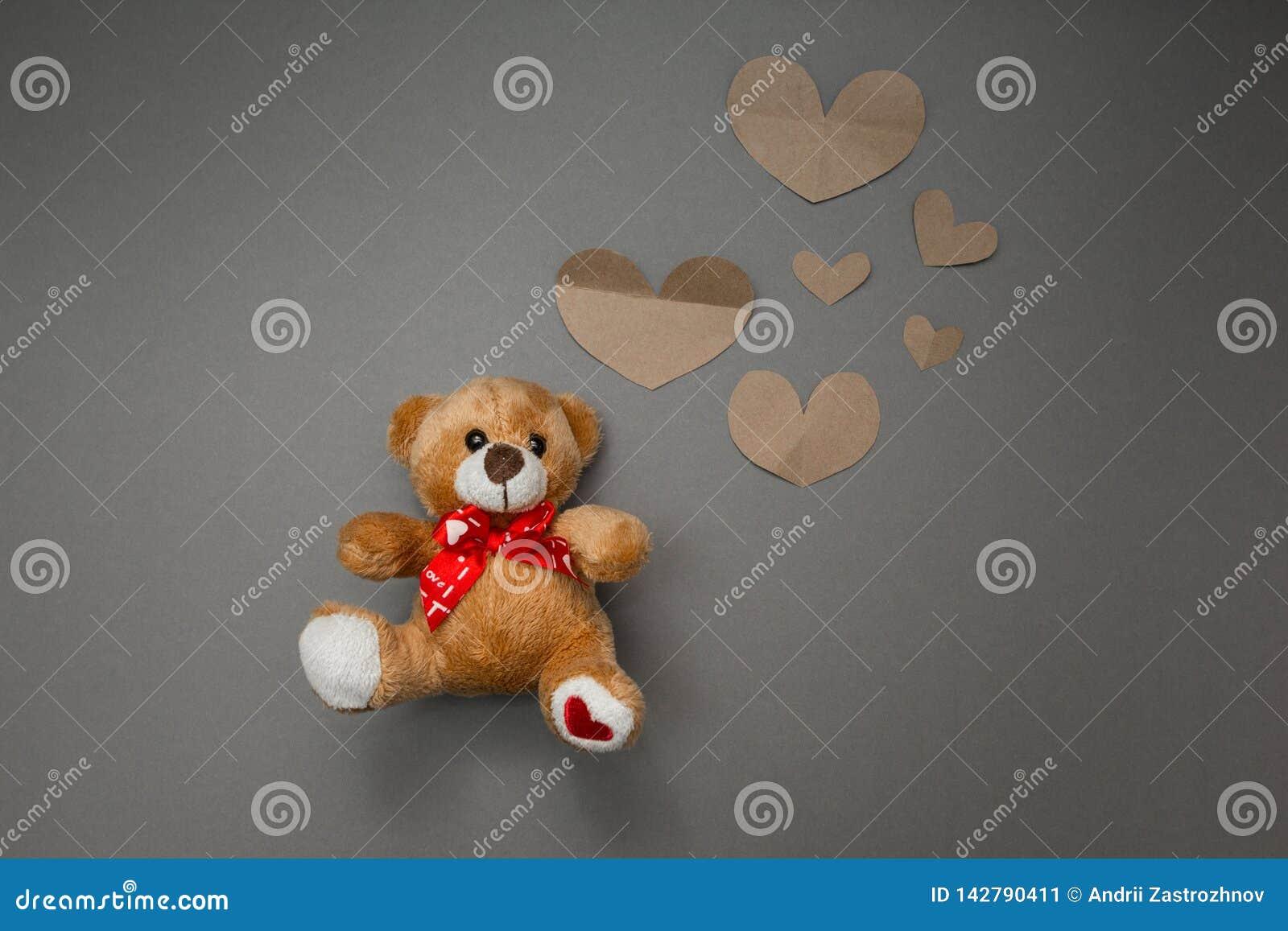 Oso de peluche y corazones de papel
