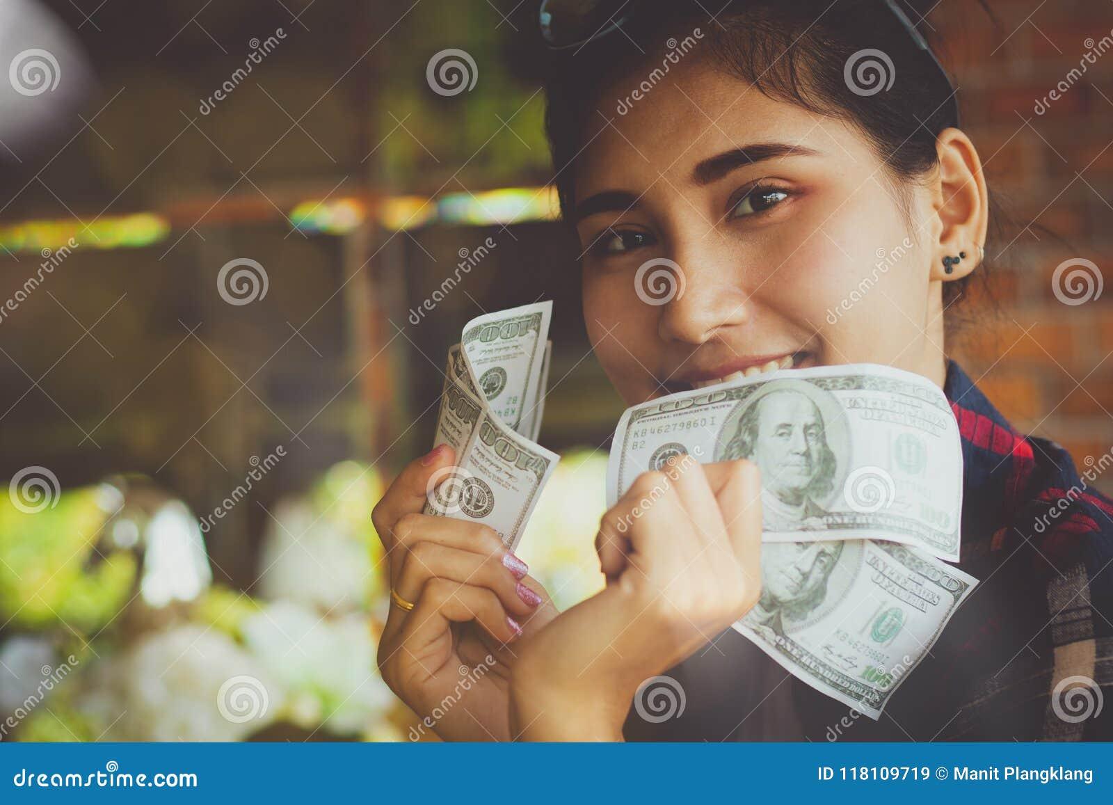 Osob ręki trzyma USA dolarów banknoty z szczęśliwym