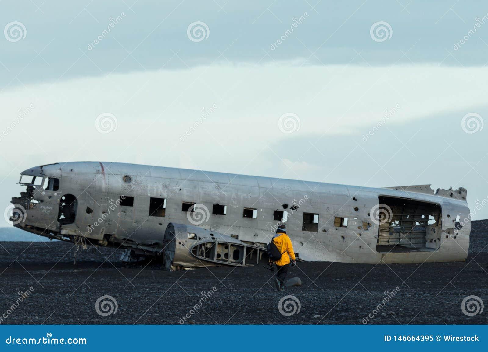 Osoba w żółtym deszczowu zbliża się starego rozbijającego samolot w polu