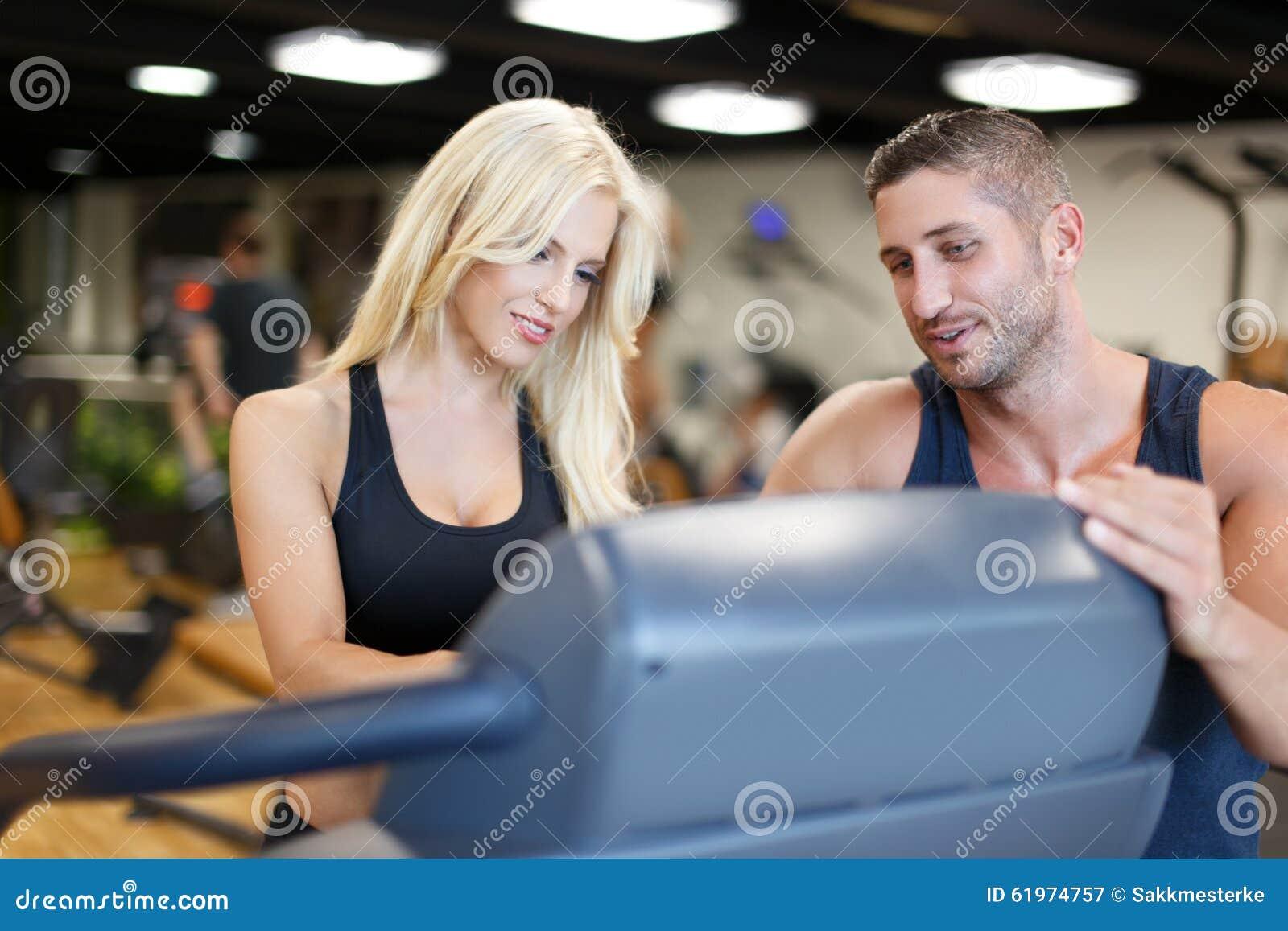 Osobisty trener pomaga blondynki kobieta w gym