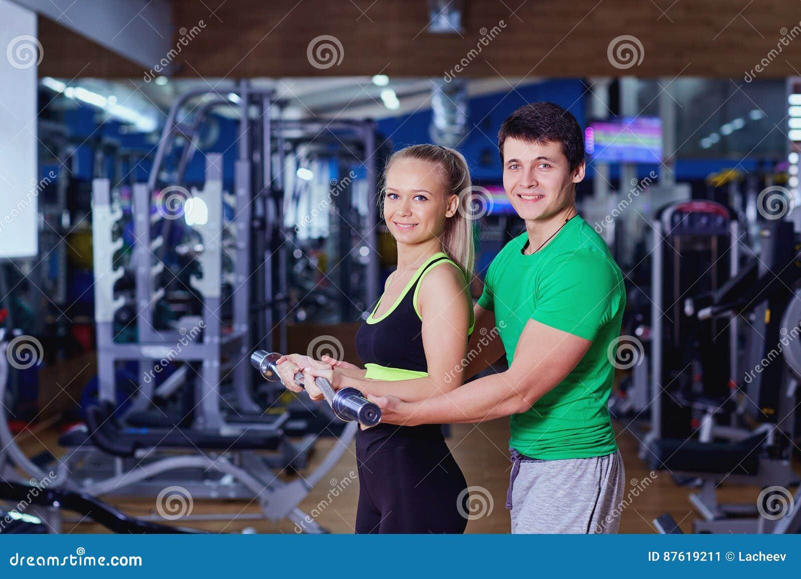 Osobisty trener pomaga dziewczyna udźwigu ciężarom w gym