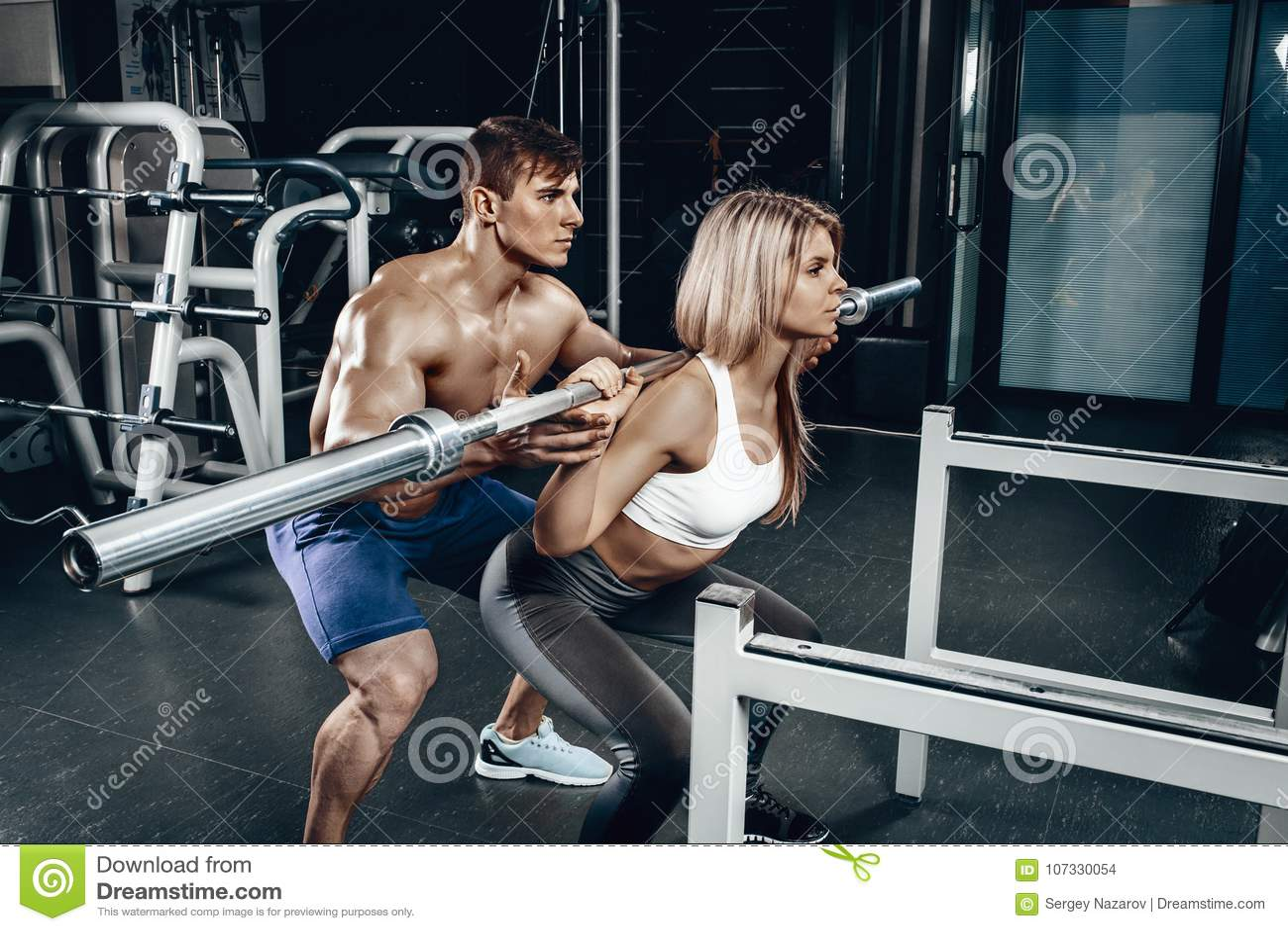 Osobisty trener pomaga młodej kobiety podnosić barbell podczas gdy pracujący w gym out