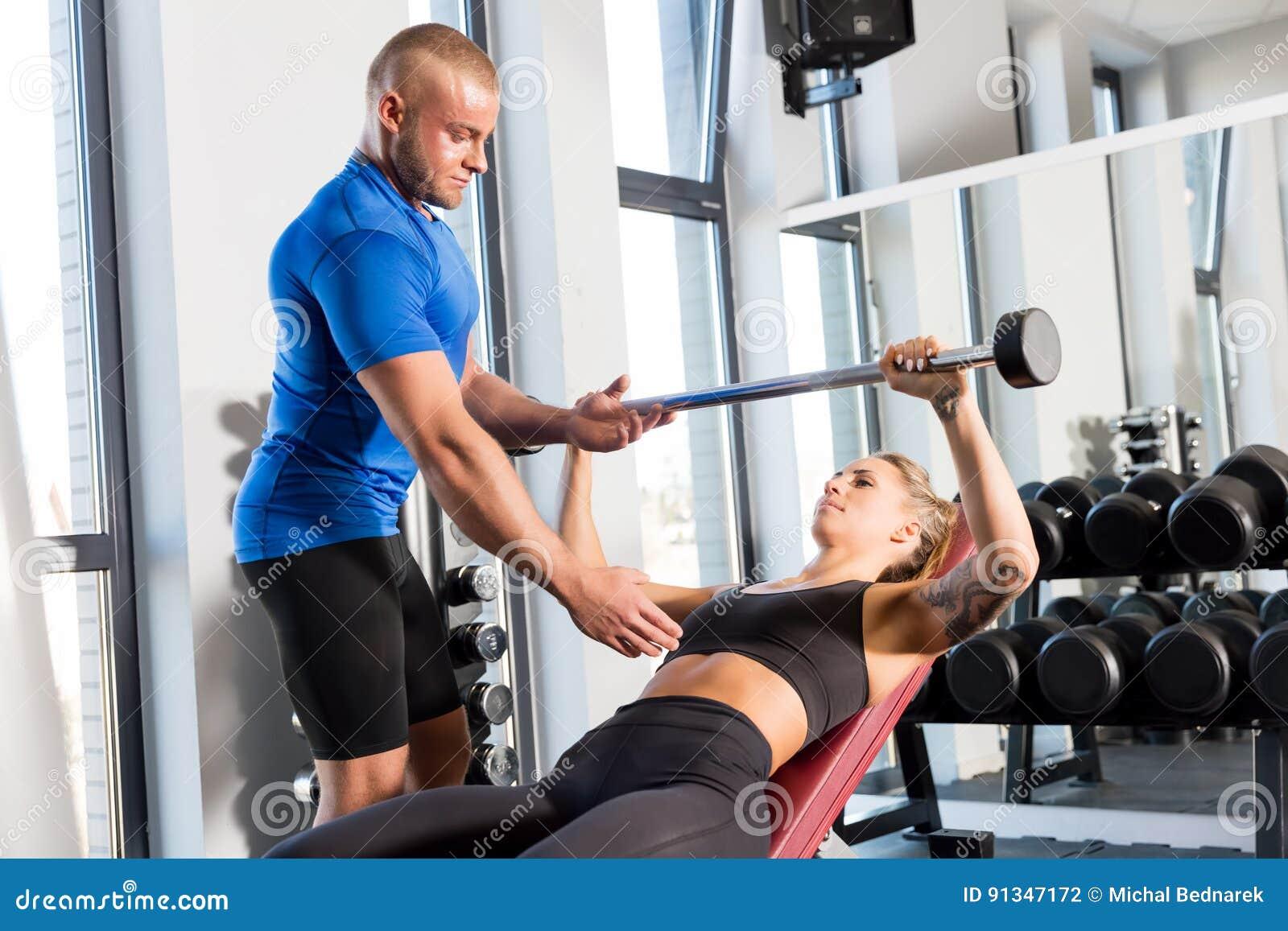 Osobisty trener pracuje z klientem przy gym