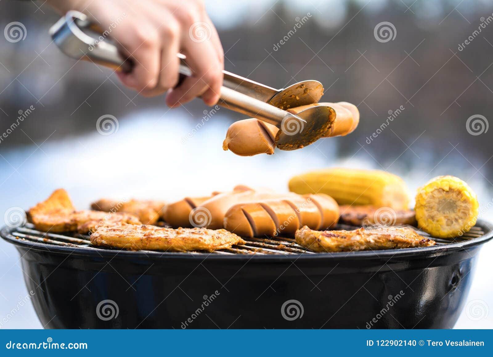Osoby opieczenie z węgla drzewnego czajnika grillem pełno jedzenie