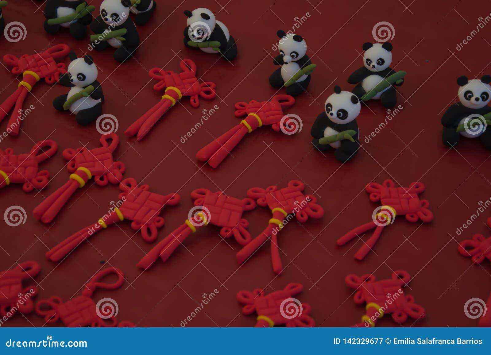 Osos de panda de la plastilina y ornamento chino del nudo con el fondo rojo