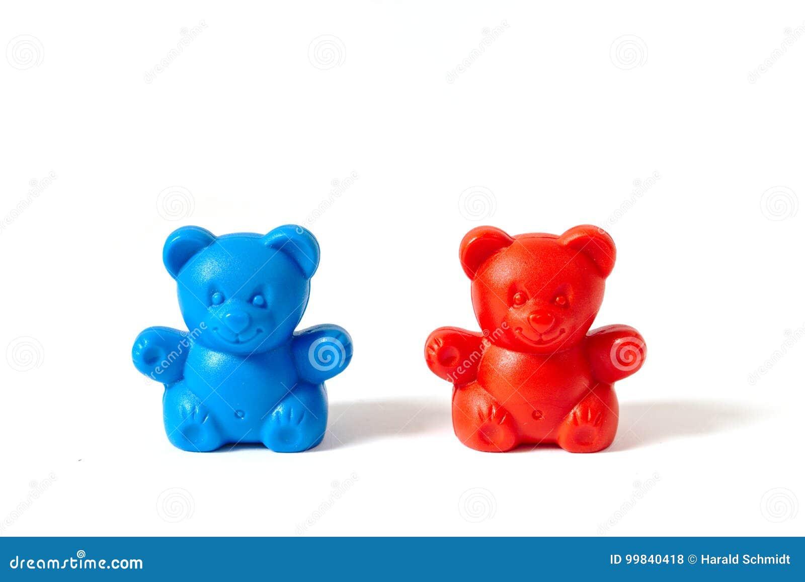 Osos plásticos rojos y azules del juguete aislados en el fondo blanco