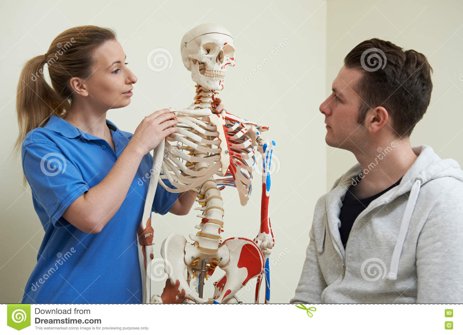 Ostéopathe discutant la blessure avec le patient à l aide du squelette