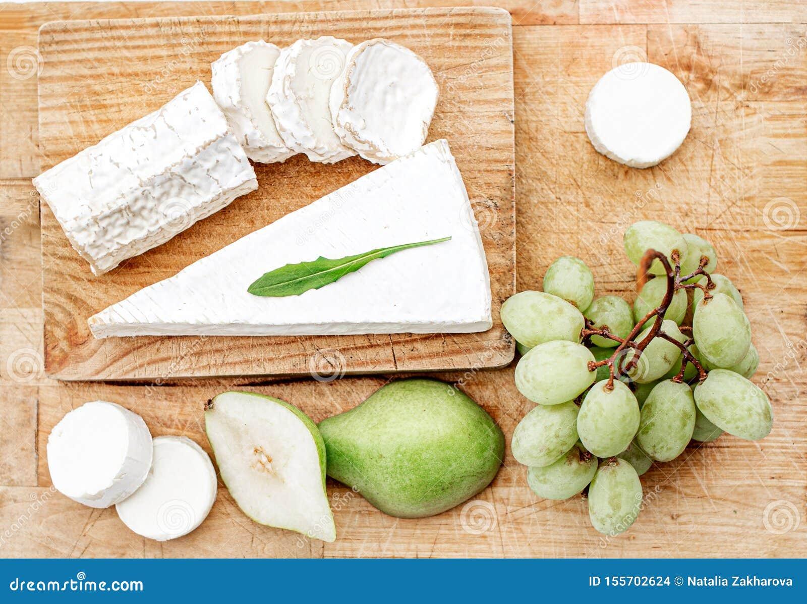 Ostbräde med det olika ost, päronet och druvor på vit träbakgrund B?sta sikt f?r ostuppl?ggningsfat kopiera avst?nd