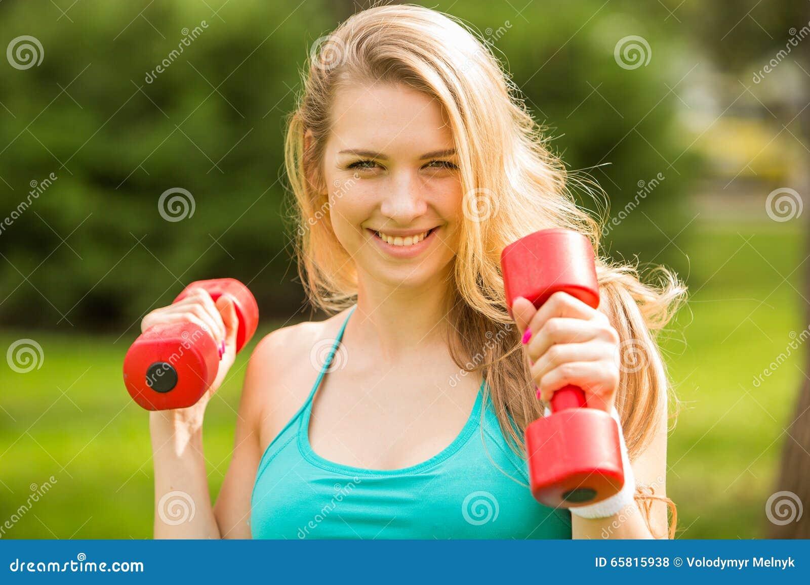 Ostenta o exercício da menina com pesos no parque