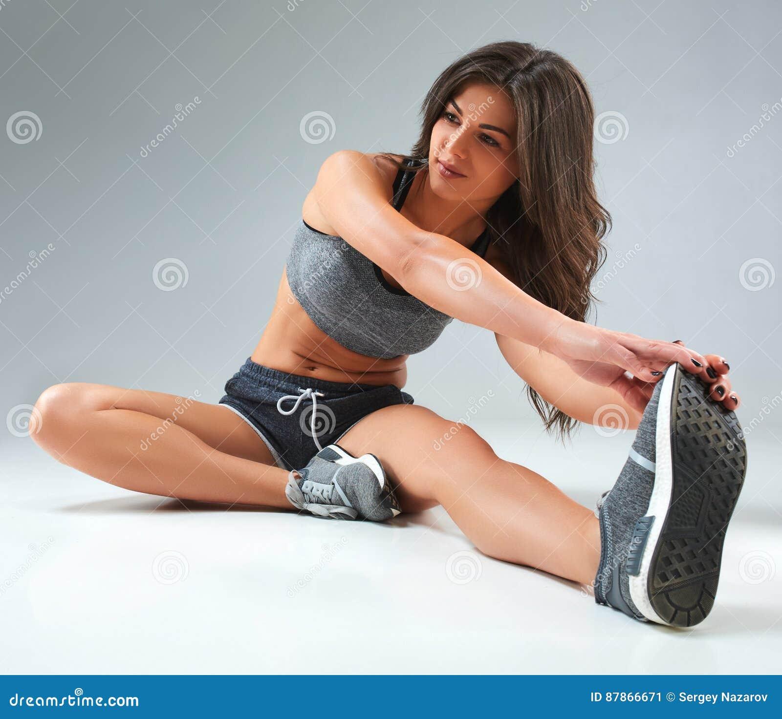 Ostente a mulher da aptidão, menina saudável nova que faz o esticão exercita no fundo cinzento
