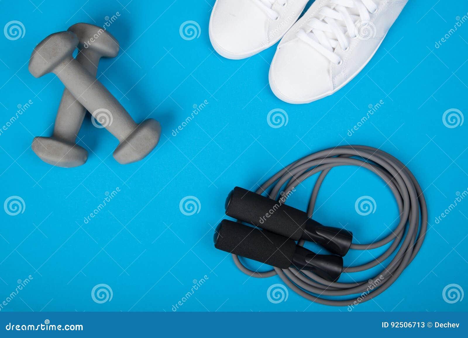 Ostente sapatas, pesos e corda de salto no fundo azul Vista superior Aptidão, esporte e conceito saudável do estilo de vida