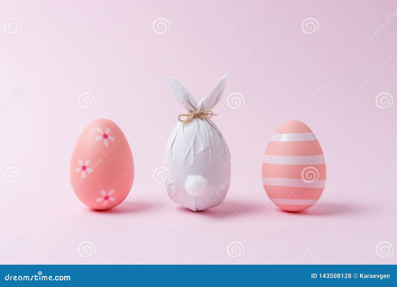 Osterei eingewickelt in einem Papier in Form eines Häschens mit bunten Ostereiern Minimales Ostern-Konzept
