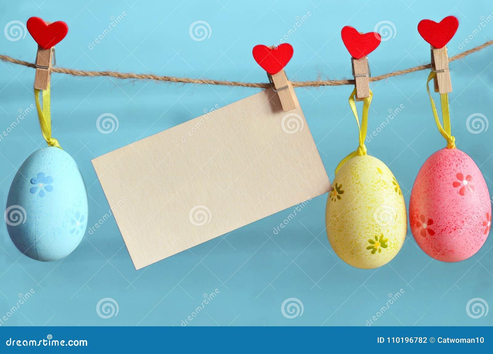 Ostereier, die am Seil auf blauem Hintergrund hängen