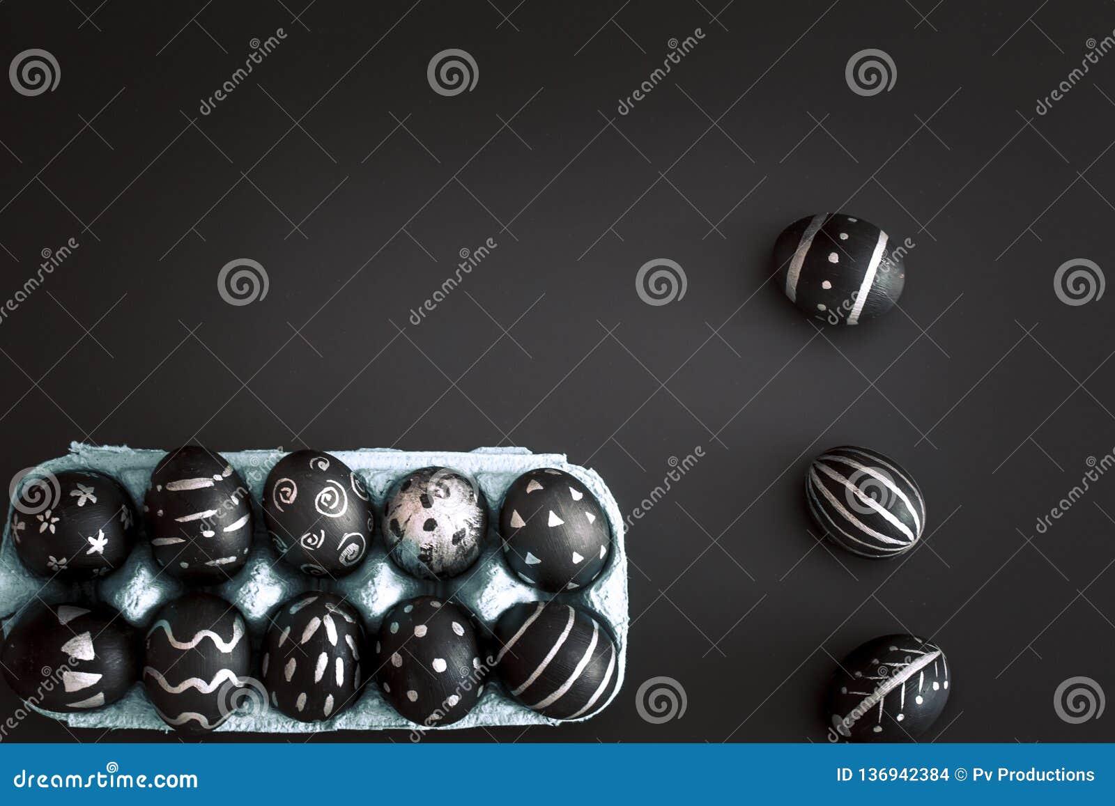 Ostereier im Behälter auf schwarzem lokalisiertem Hintergrund