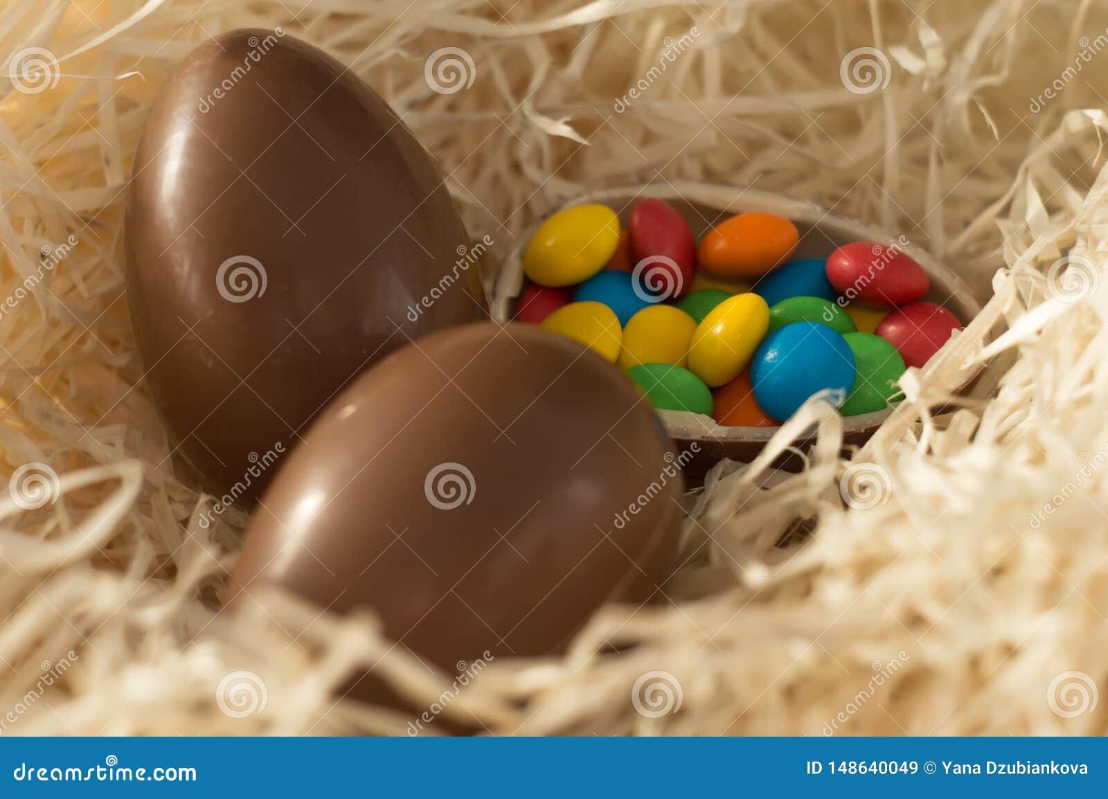 Ostern Schokoladeneier mit mehrfarbigen S??igkeiten liegen in einem Nest auf einer h?lzernen wei?en Tabelle