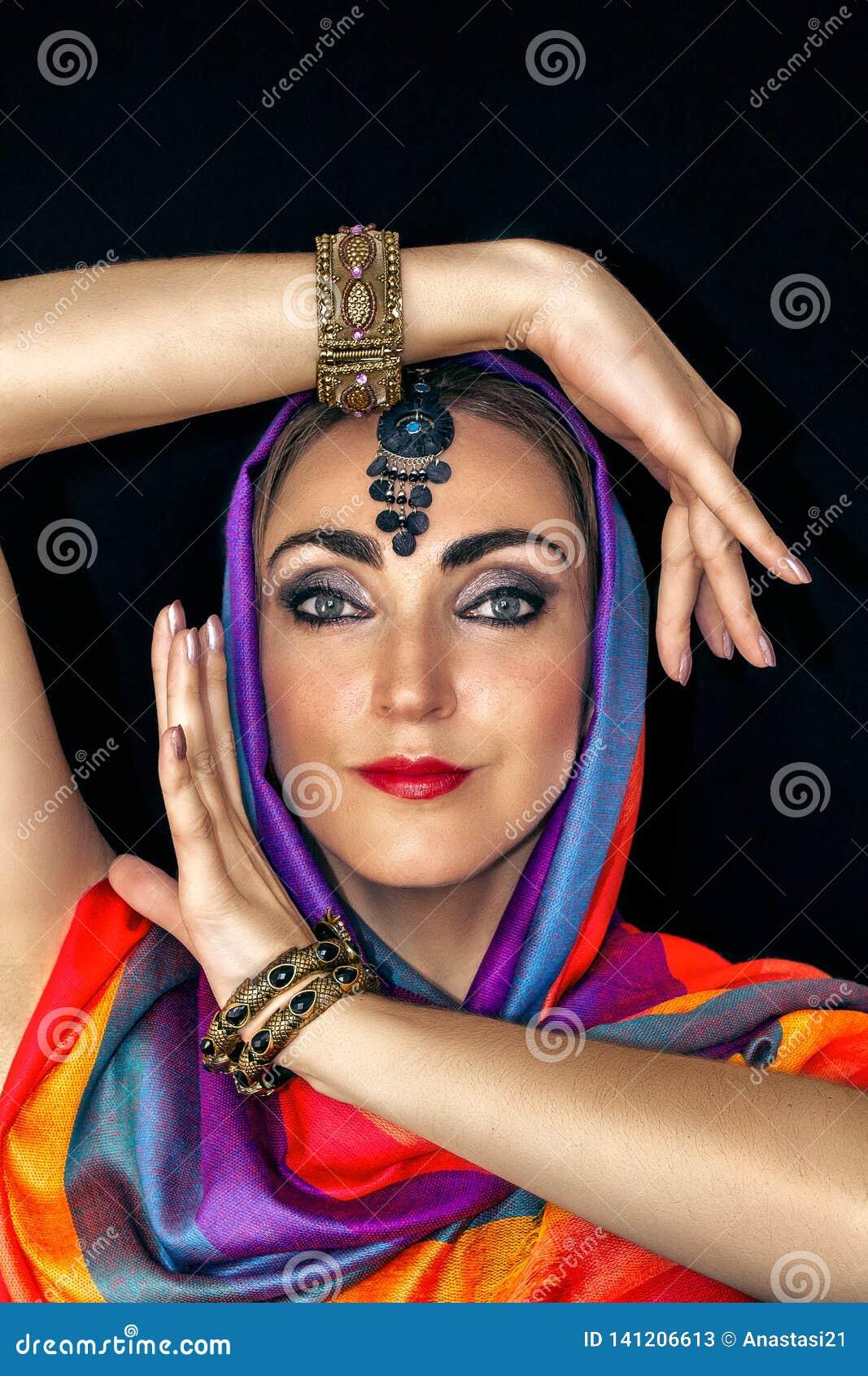 Ostfrau im burqa mit Juwelen auf einem schwarzen Hintergrund