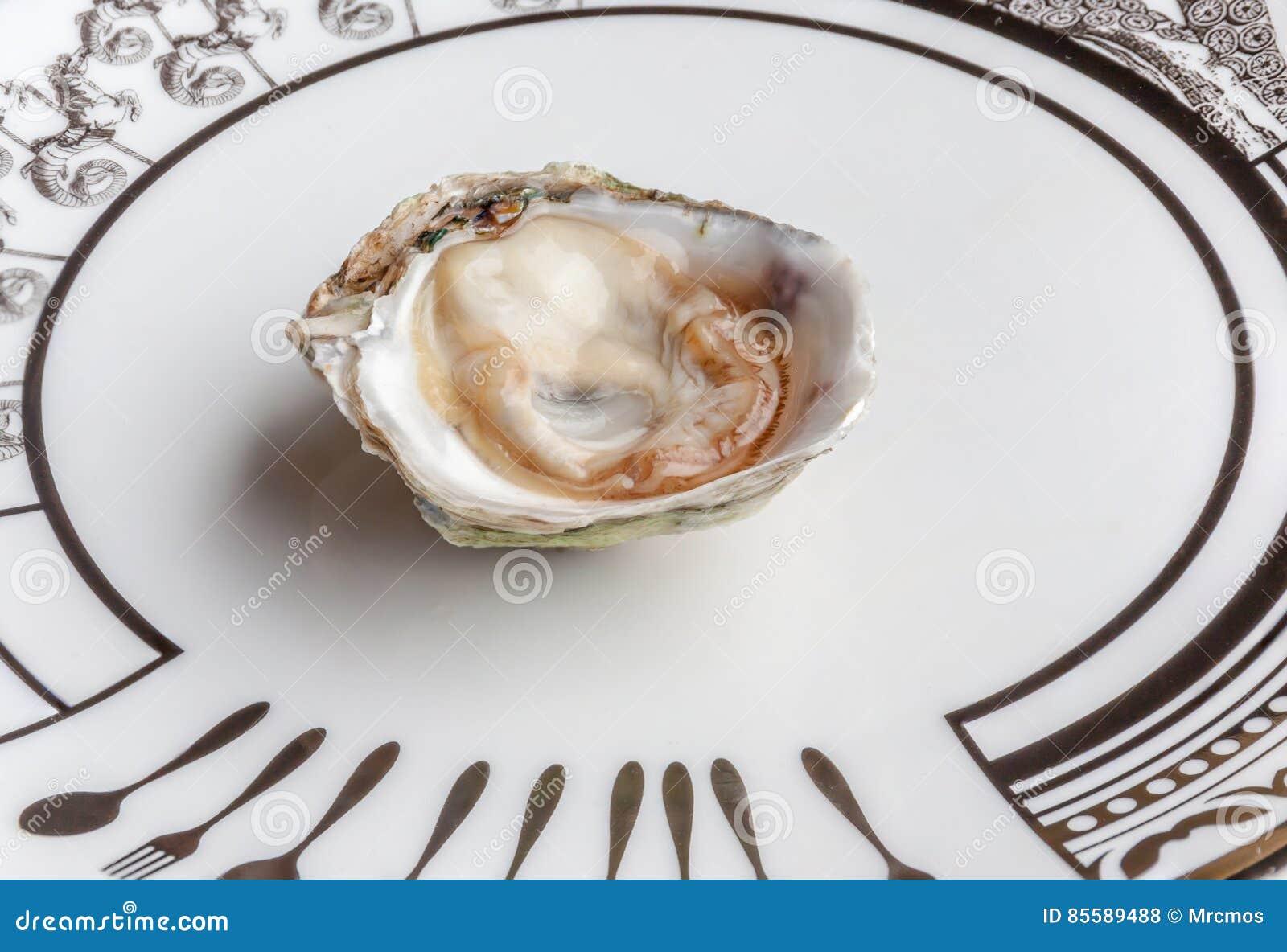 A ostra fresca e suculenta crua aberta serviu na placa cerâmica luxuosa