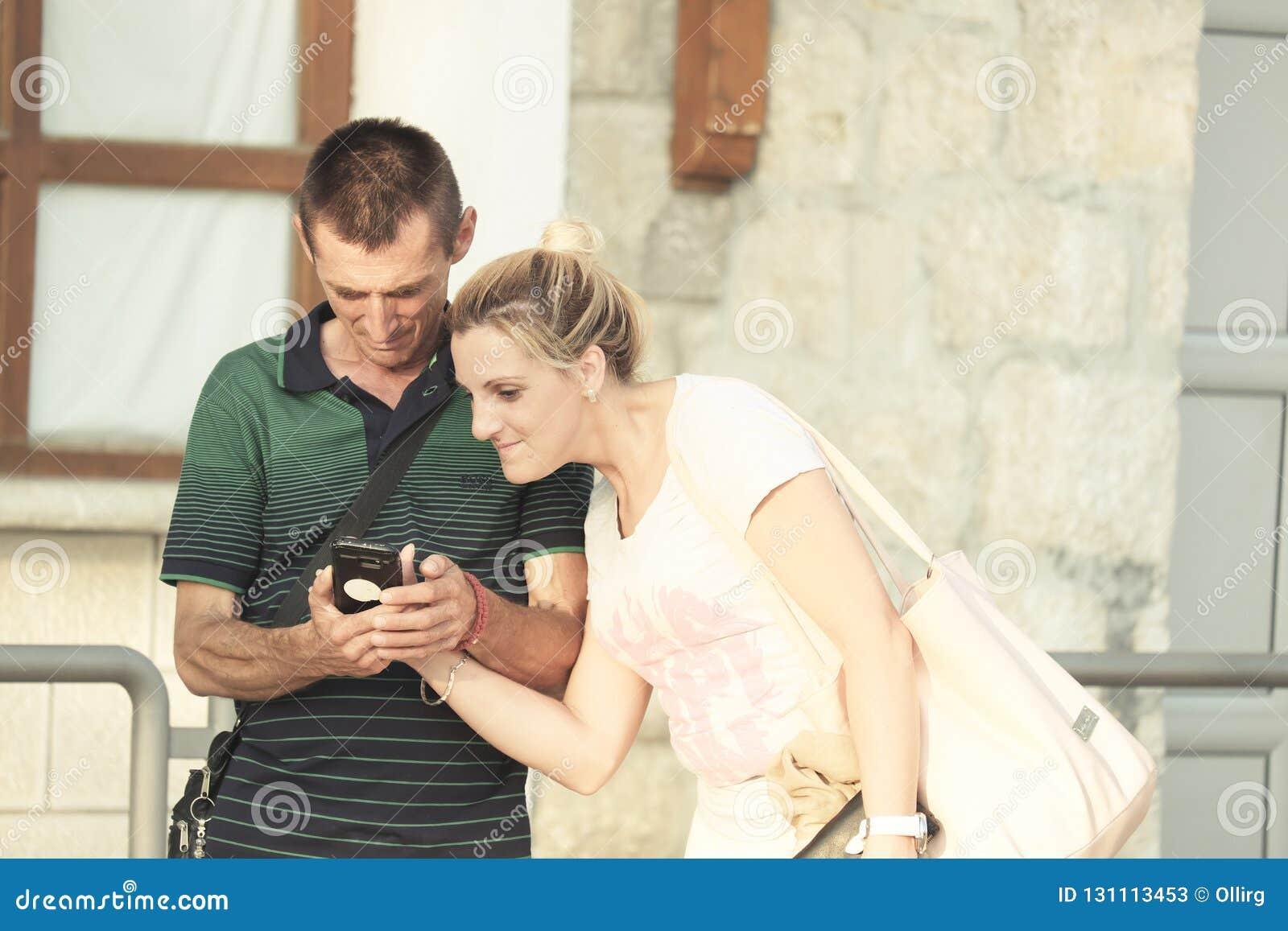 Adult Couple Are Looking Smartphone, Ostrog Monastery - Montenegro