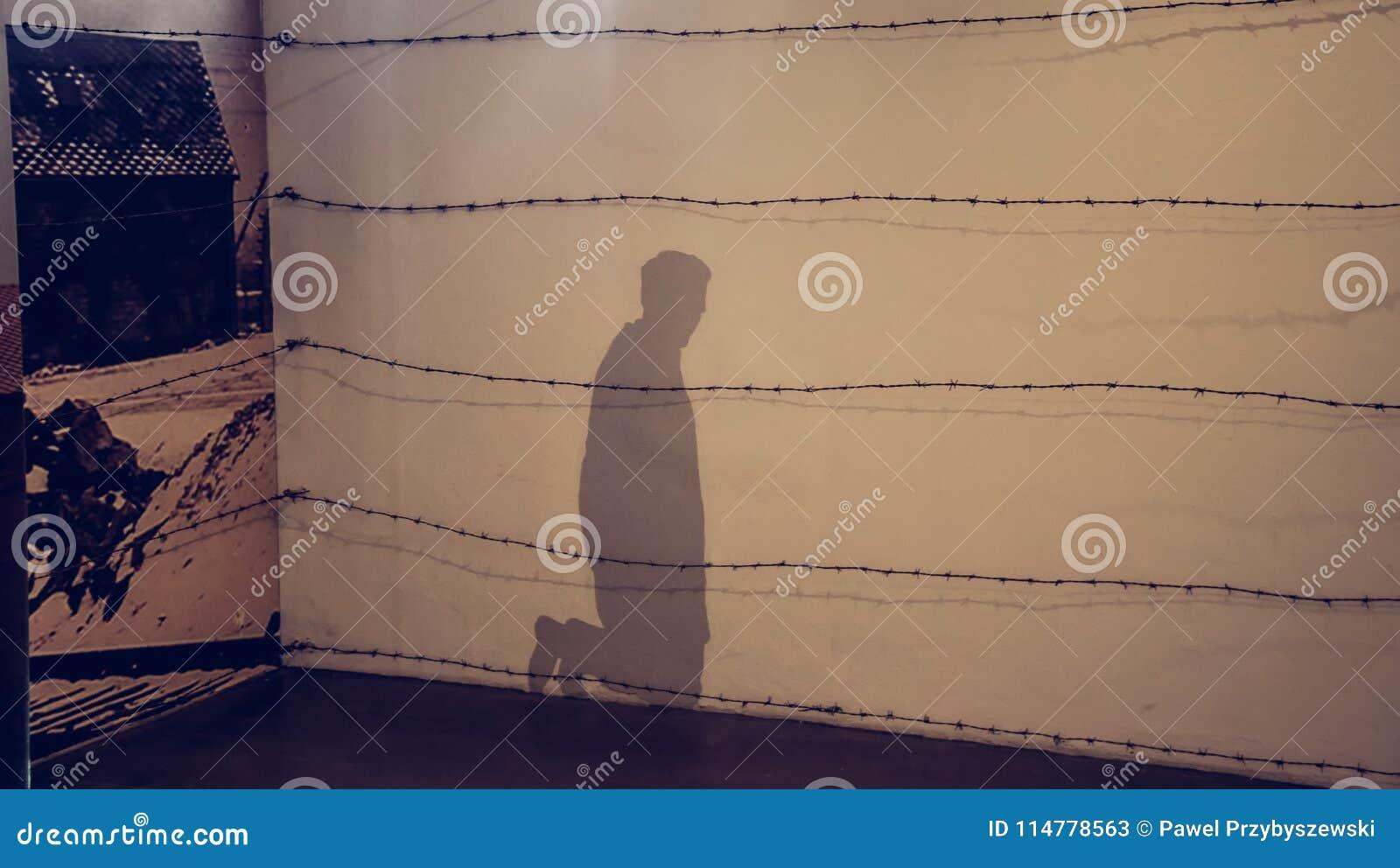 Oswiecim, Polska/- 02 15 2018: Cień na ścianie klęczenie mężczyzna