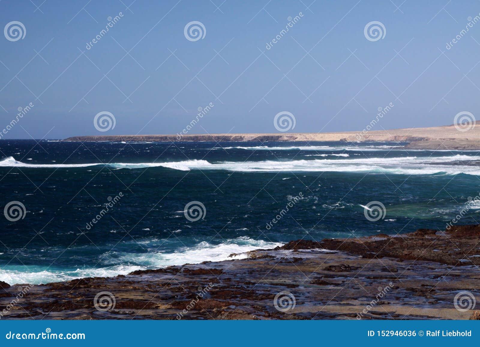Oszałamiająco naturalny punkt widzenia z nagimi suchymi wzgórzami, turkusową laguną i wściekłym dzikim morzem przy północnego zac