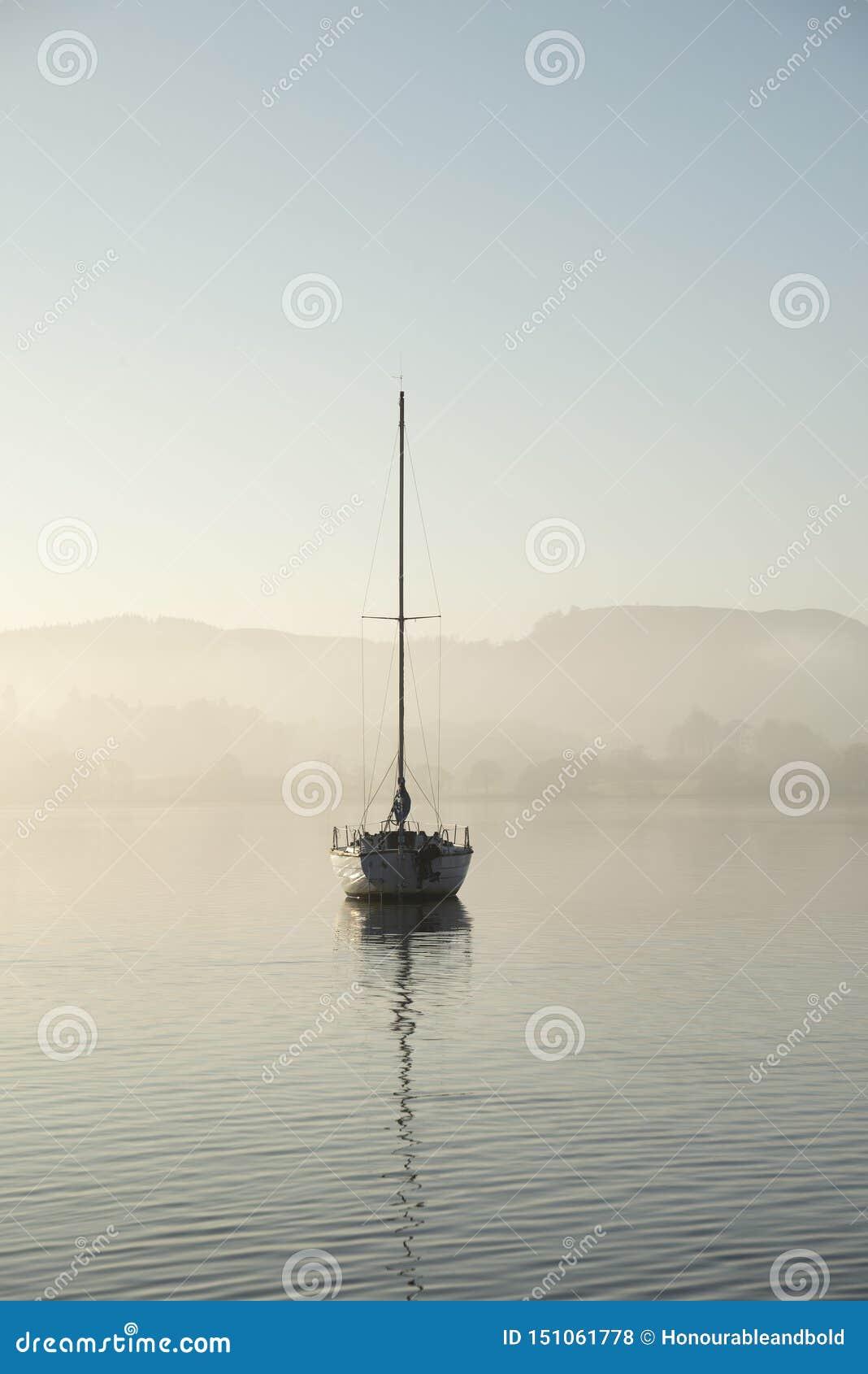 Oszałamiająco niezatamowany sztuka piękna krajobrazu wizerunek siedzi wciąż w spokojnej jezioro wodzie w Jeziornym okręgu podczas
