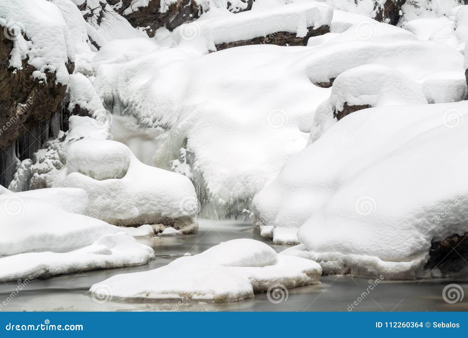 Oszałamiająco zima krajobraz, kamienie na mroźnej rzece zakrywał śnieg a