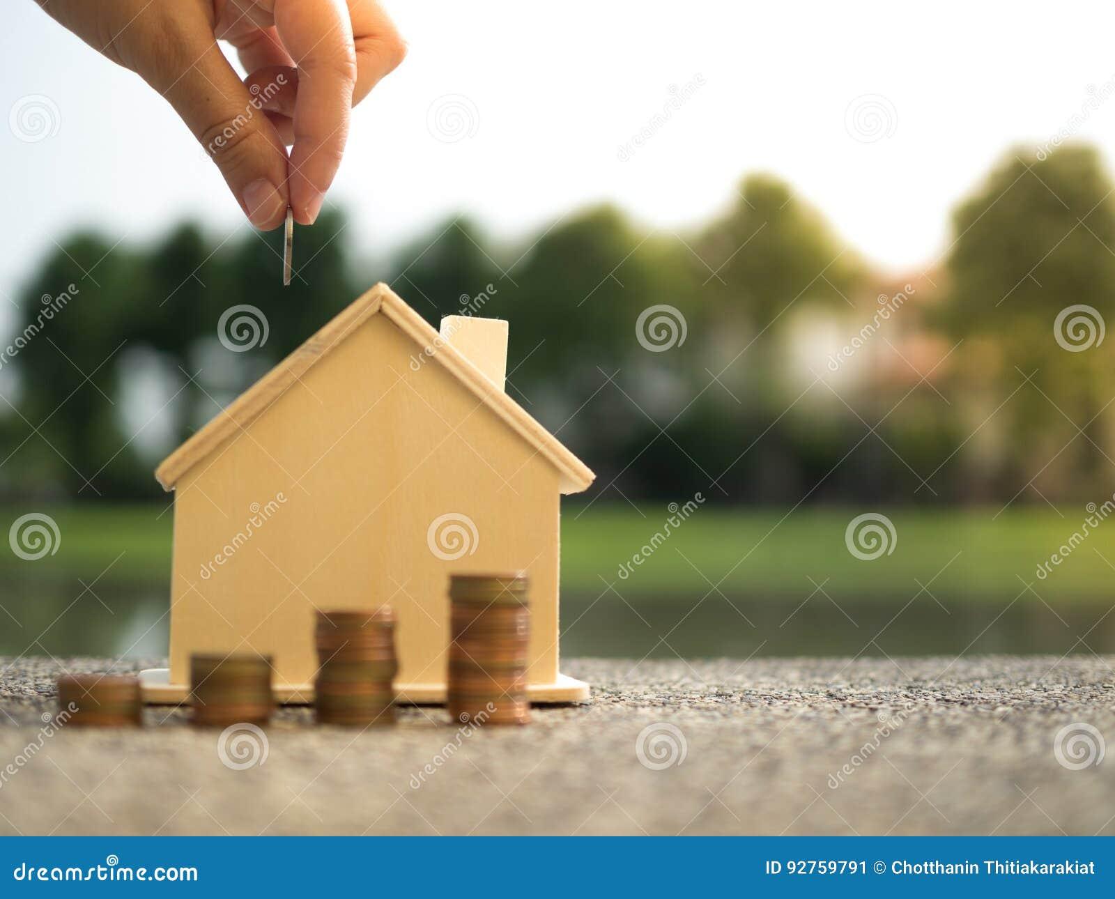 Oszczędzanie kupować dom który wręcza kładzenie pieniądze monet sterty dorośnięcia, oszczędzanie pieniądze lub pieniądze przyrost