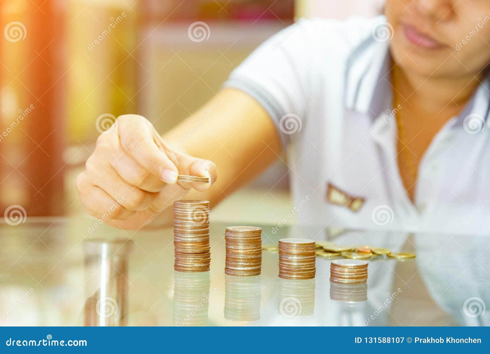 Oszczędzanie pieniądze pojęcia, kobiety sztaplowania monety w wzrastające kolumny