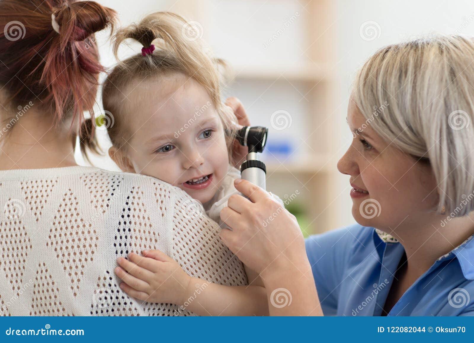 Oto-rhino-laryngologiste du ` s d enfant faisant l examen d oreille de la petite fille