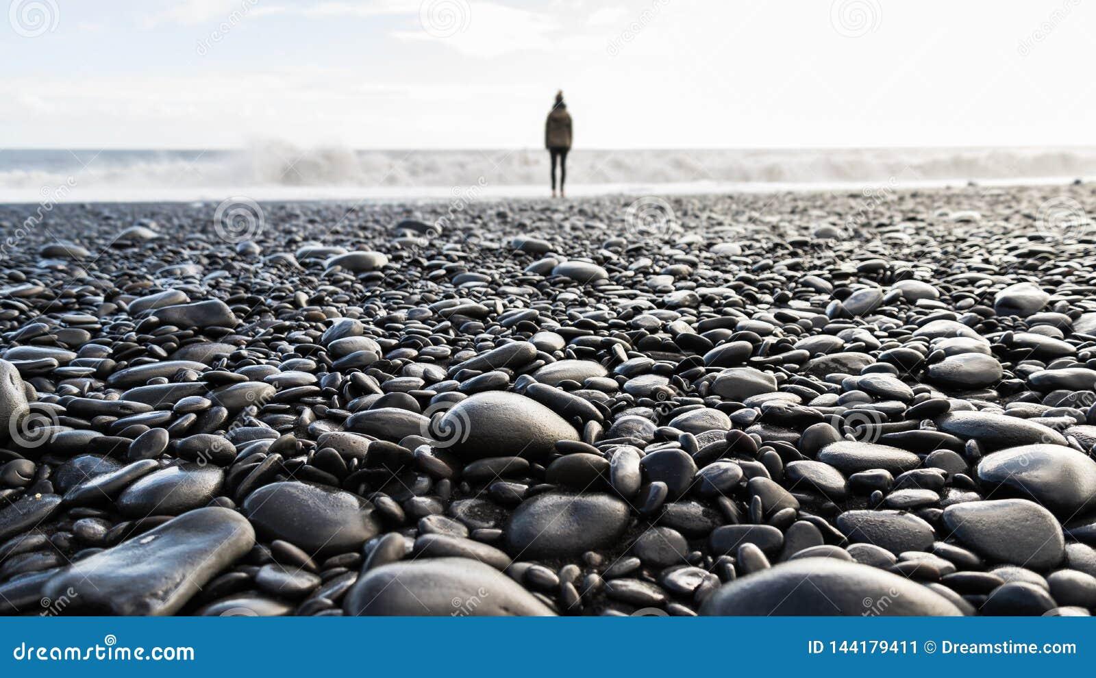 Otoczak plaża z zamazaną osoby pozycją w tle