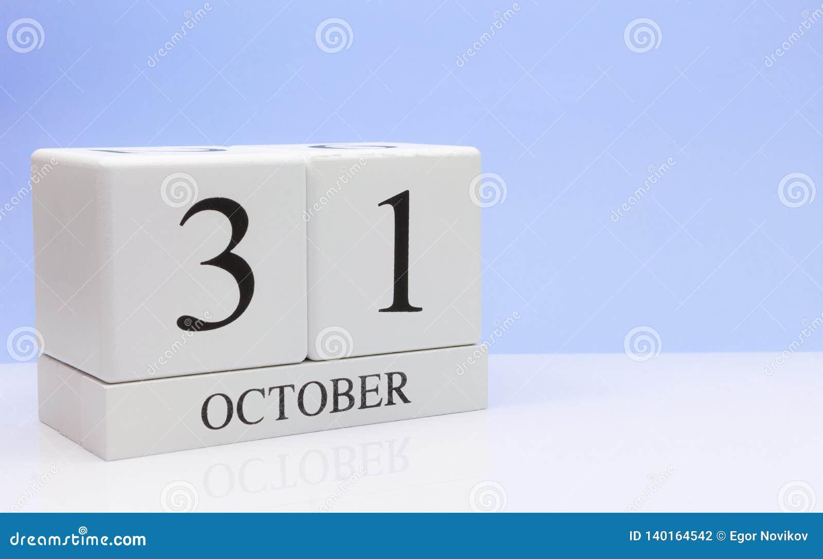 31 ottobre giorno 31 del mese, calendario quotidiano sulla tavola bianca con la riflessione, con fondo blu-chiaro Tempo di autunn