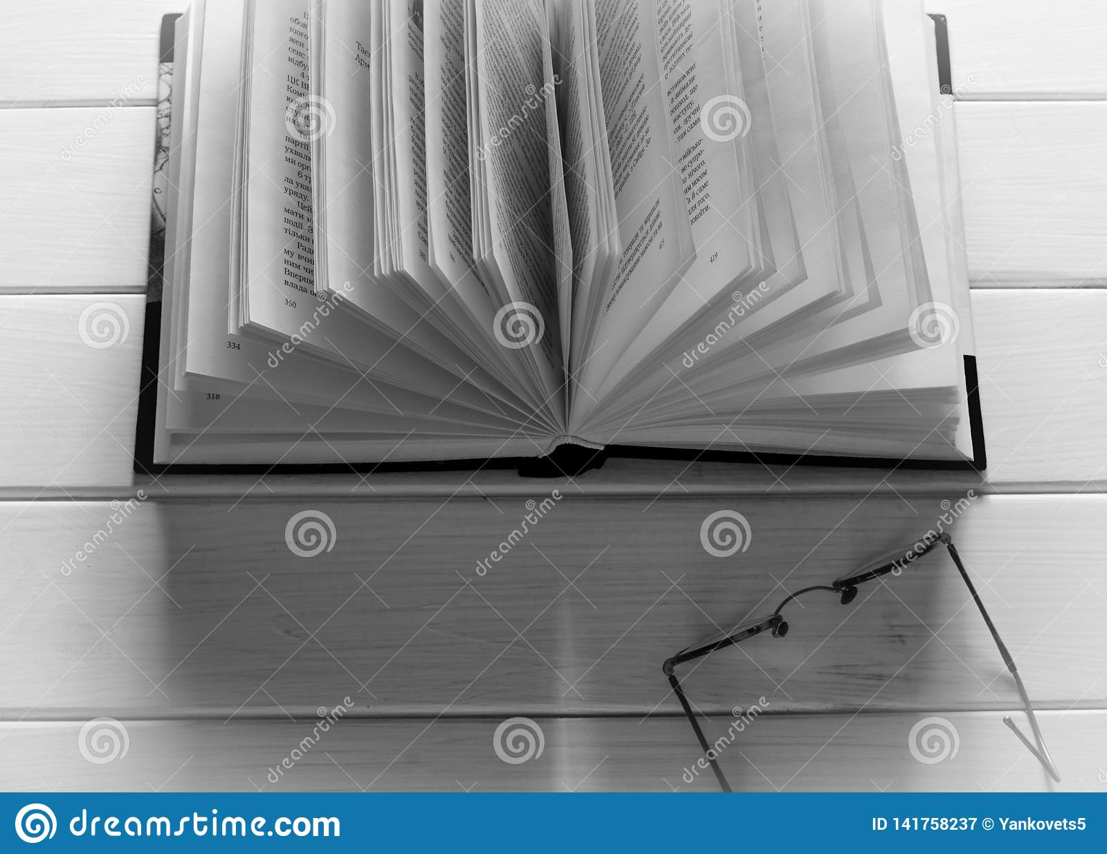 Otwarta książka gotowa czytać kłamstwa na białym drewno stole obok starych round szkieł