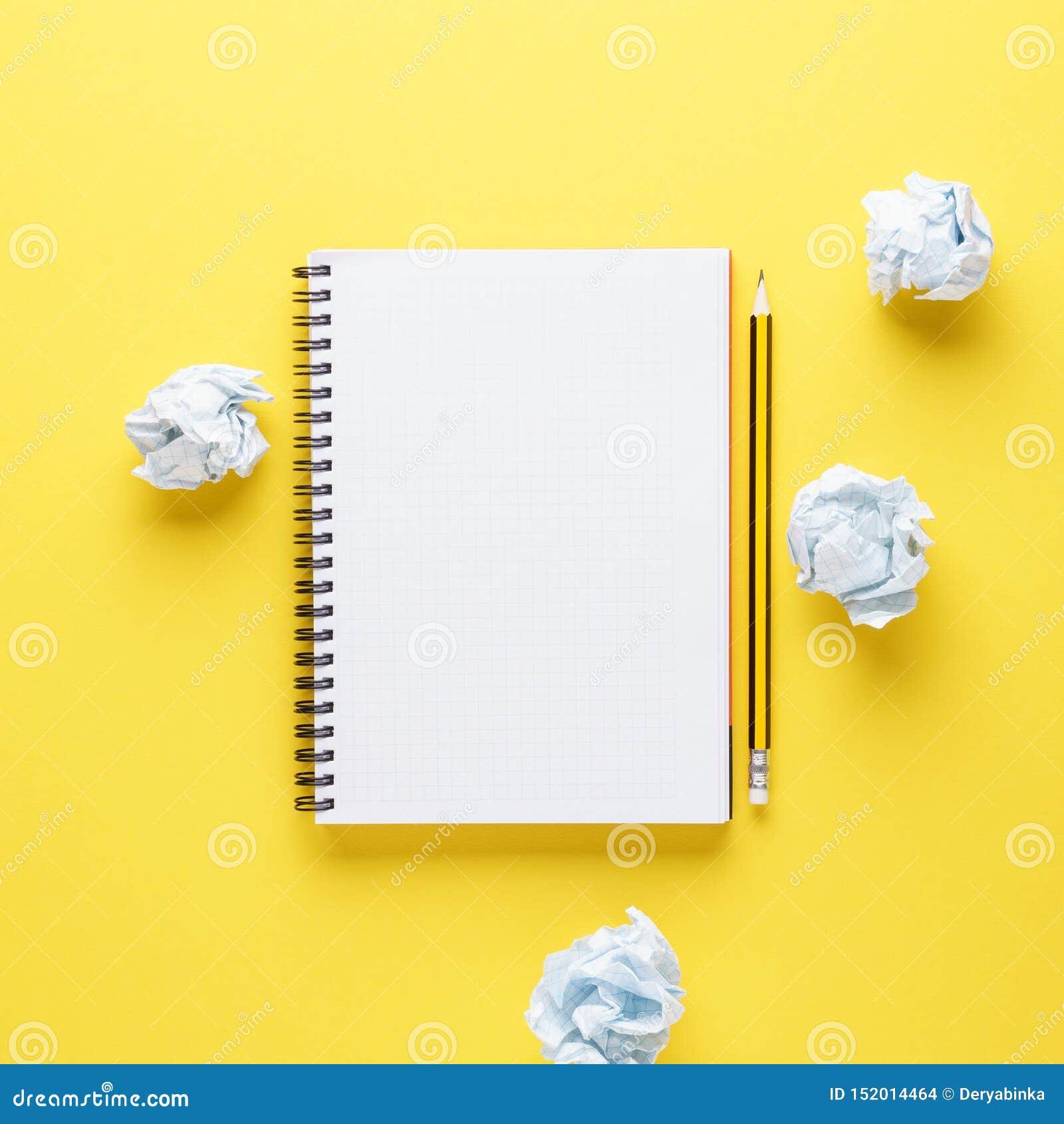 Otwarty notatnik, ołówek i miący papiery na żółtym tle,