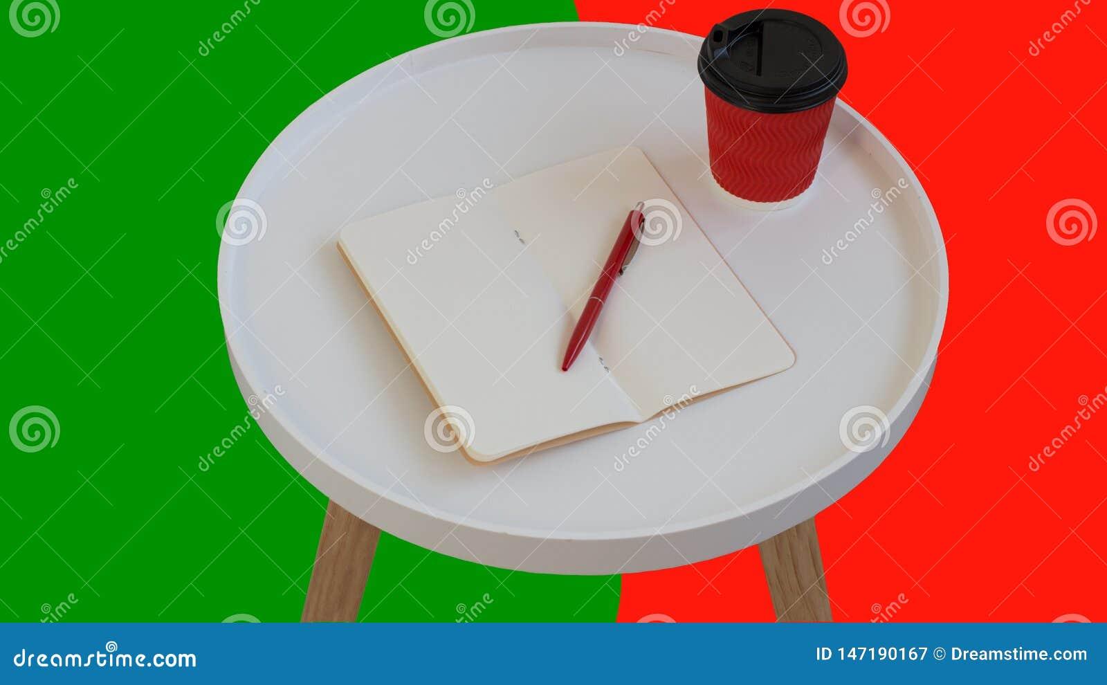Otwarty pusty pusty nutowy papier z czerwonym pi?rem, czerwony kartonowy fili?anka kawy i?? na bia?ym round czasopisma drewna sto