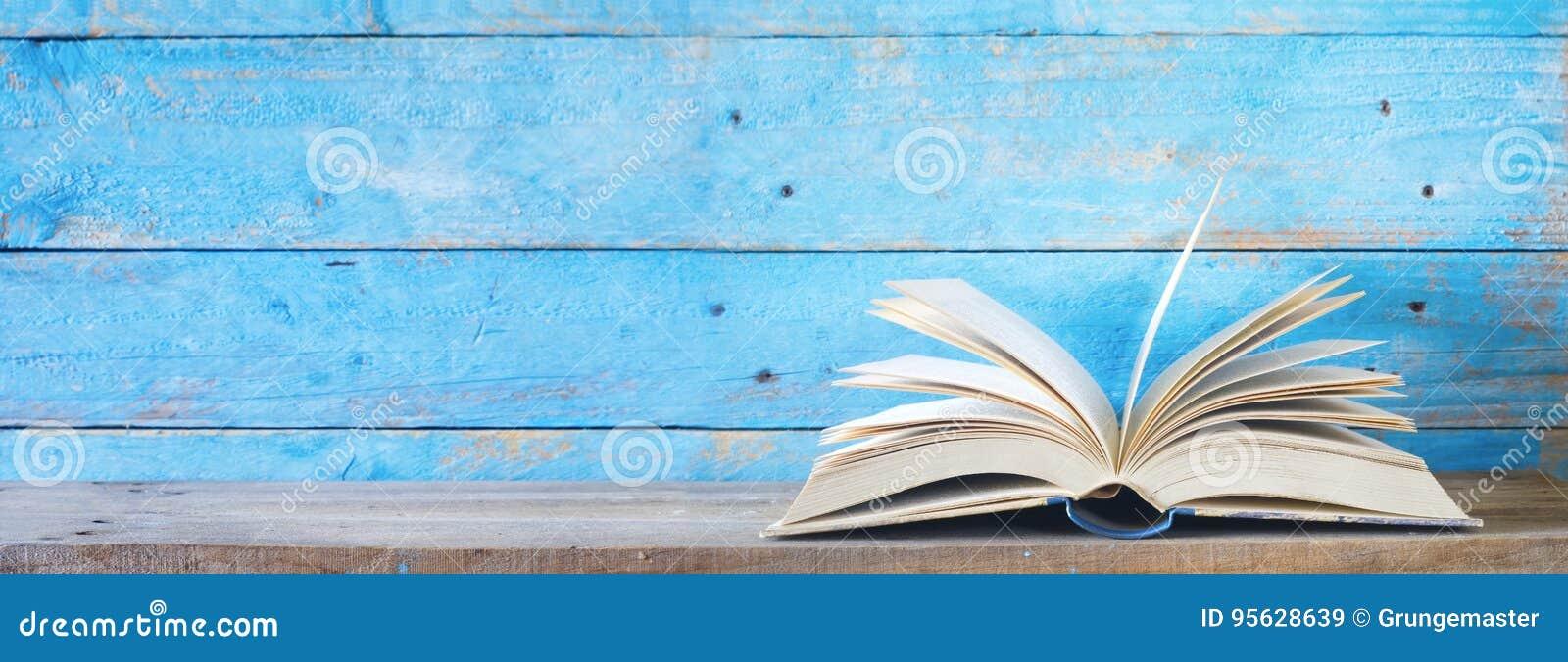 Otwiera książkę na błękitnym grungy tle