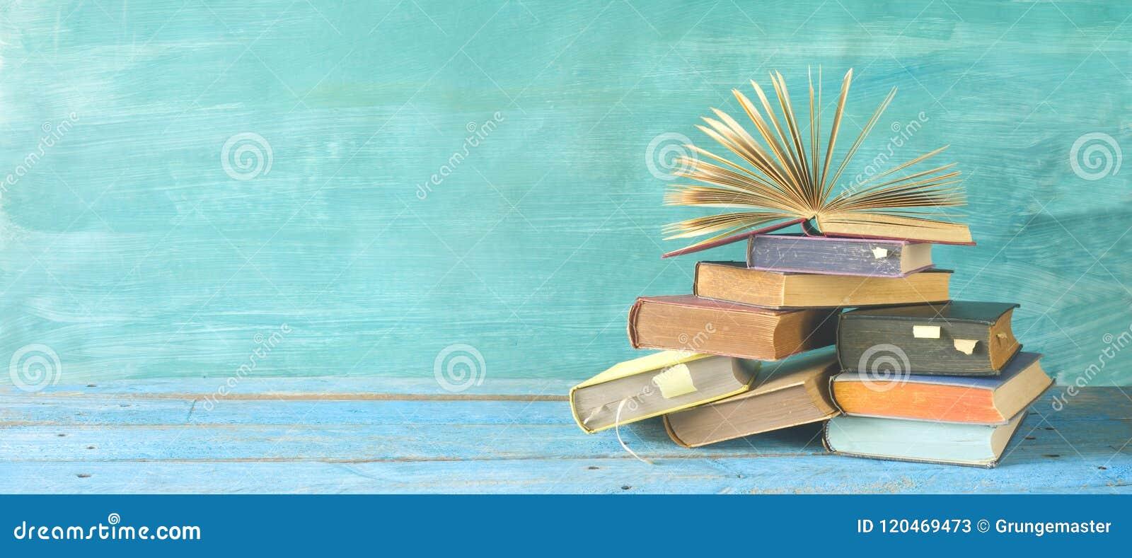 Otwiera książkę na stercie książki