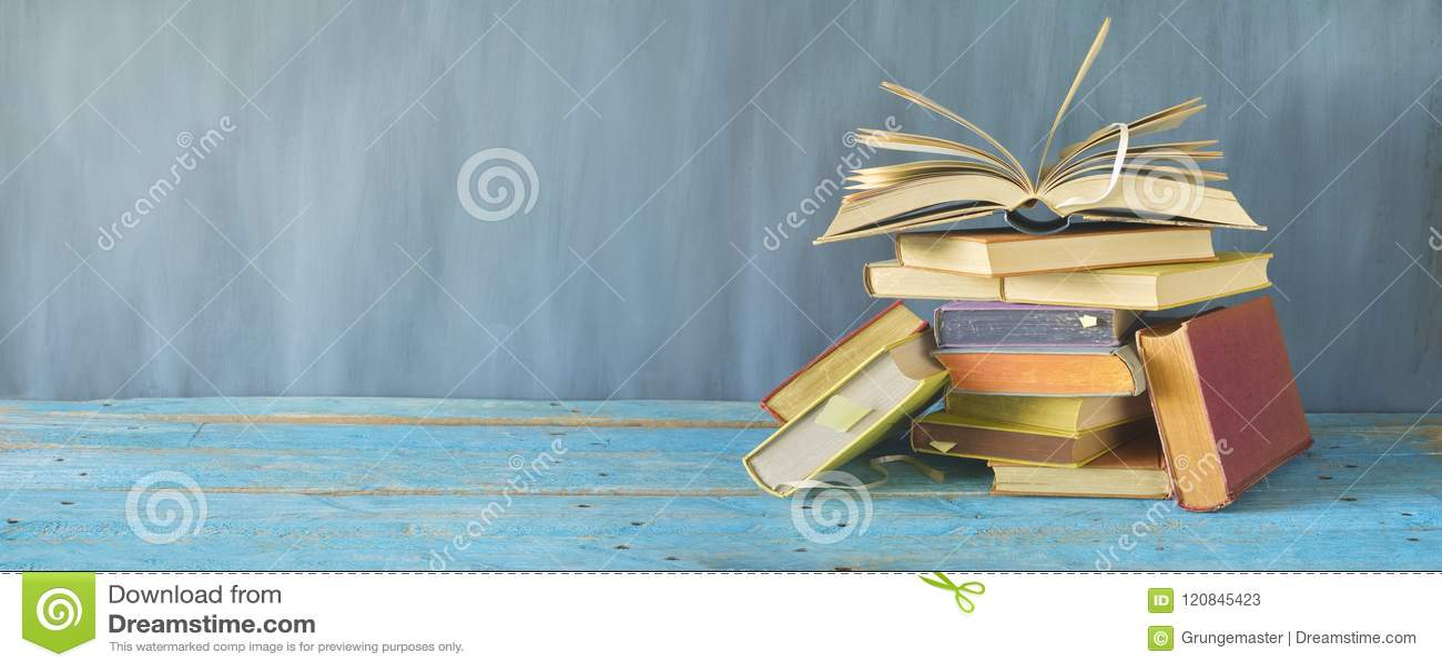 Otwiera książkę na stosie stare książki, panorama