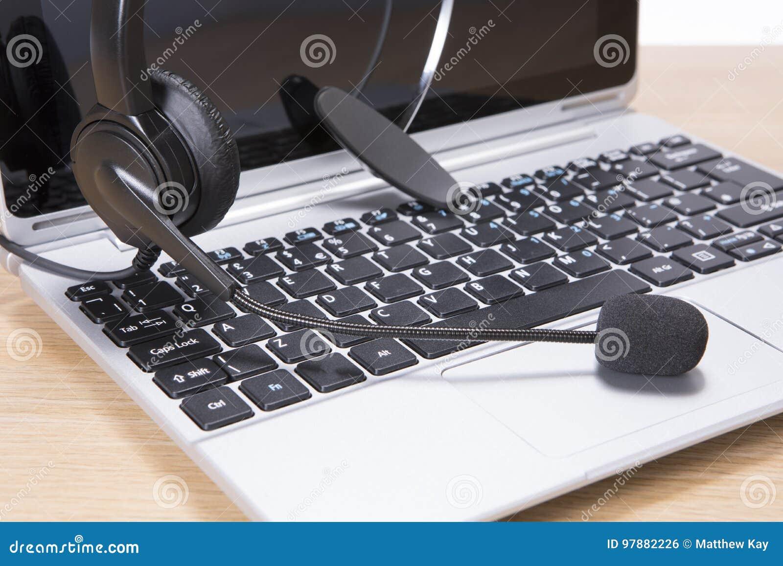 Otwiera laptop i słuchawki w komunikacyjnym pojęciu
