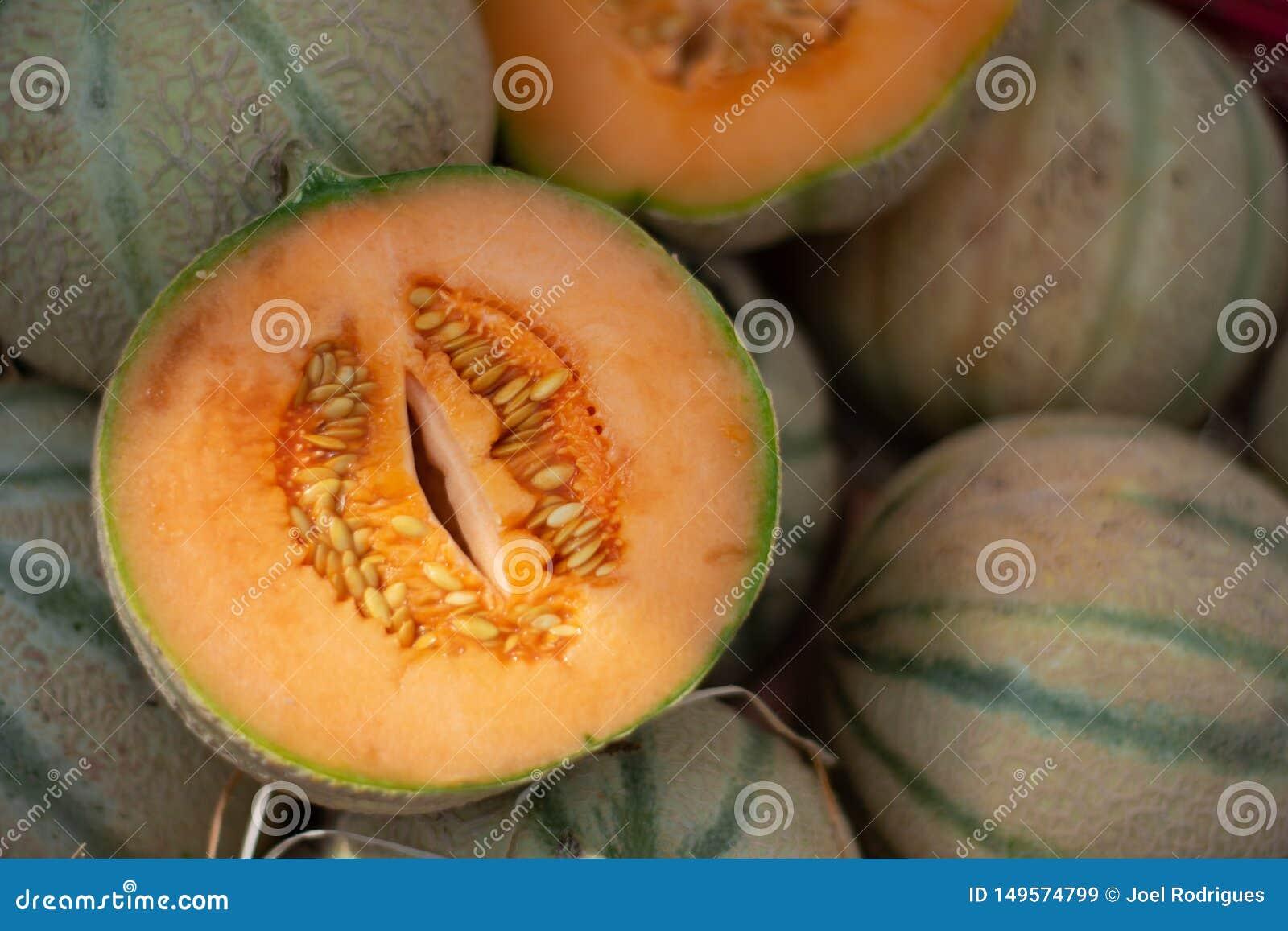 Otwiera rżniętego Charentais melon na rynku stosie