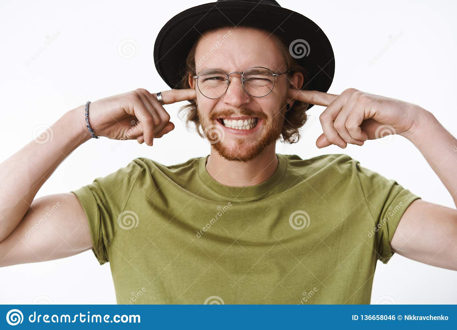 Ouch doend walgen lawaai Ontstemde intense mannelijke bandleider in glazen en hoed met baard en doordringende sluitende oren met
