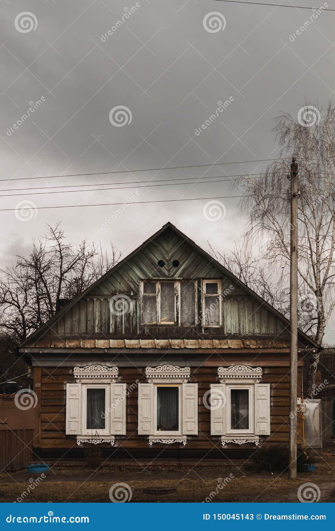 Oud blokhuis met witte blinden in bewolkt weer