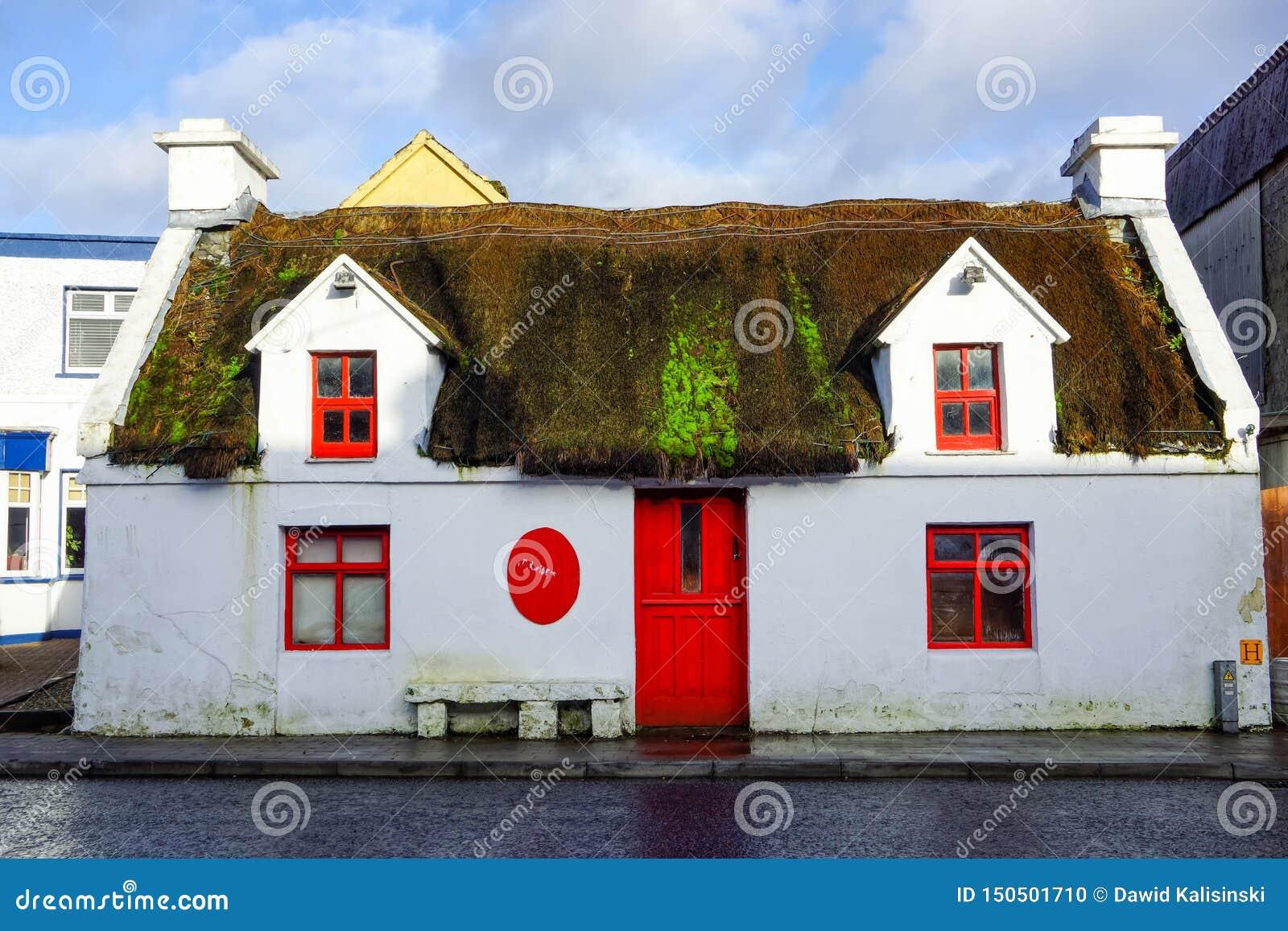 Oud geruïneerd en verlaten met stro bedekt huis met rode vensters en deur