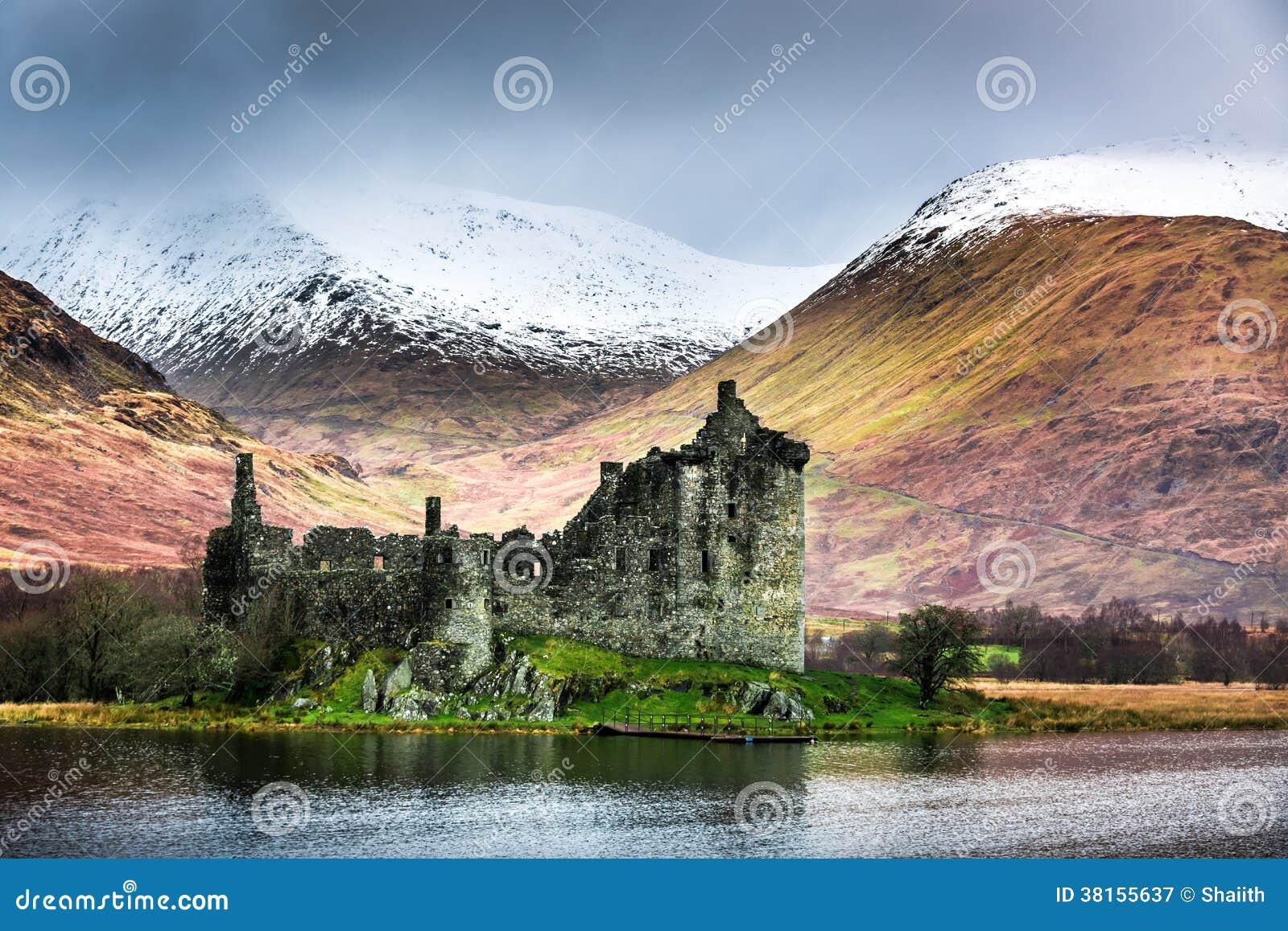 Oud geruïneerd kasteel op de achtergrond van sneeuwbergen