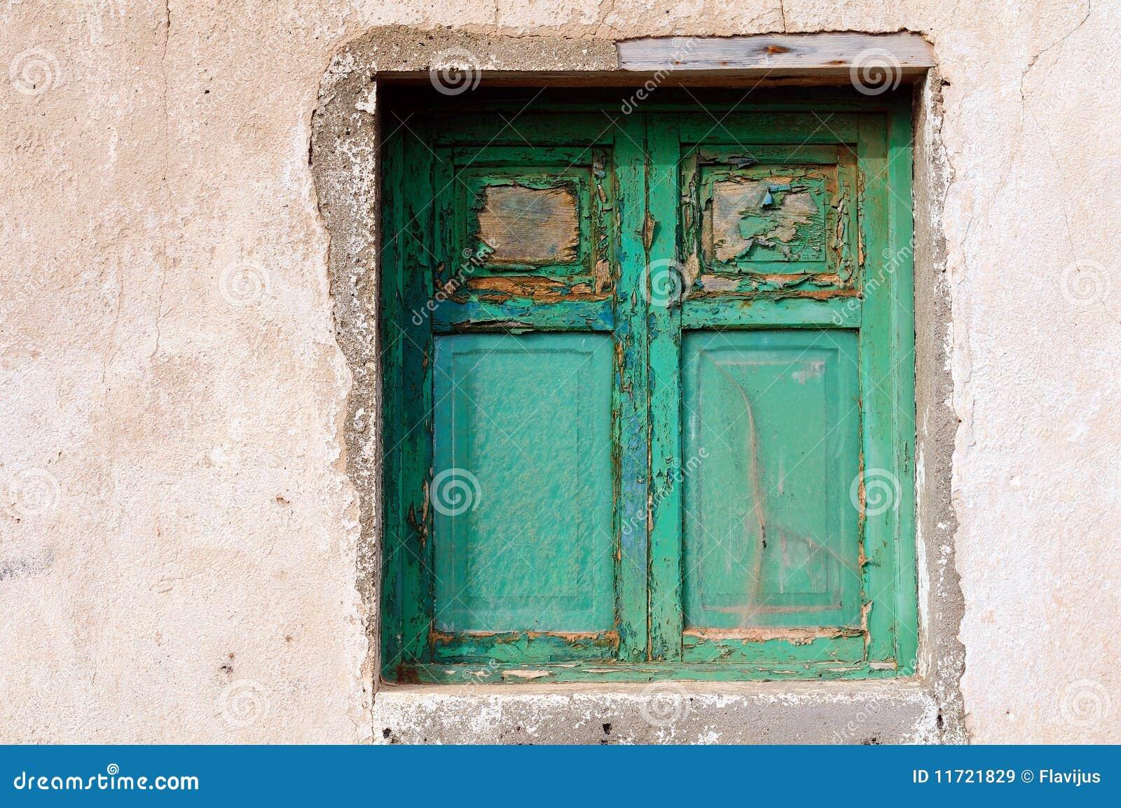 Oud groen venster op de verlaten oude muur.