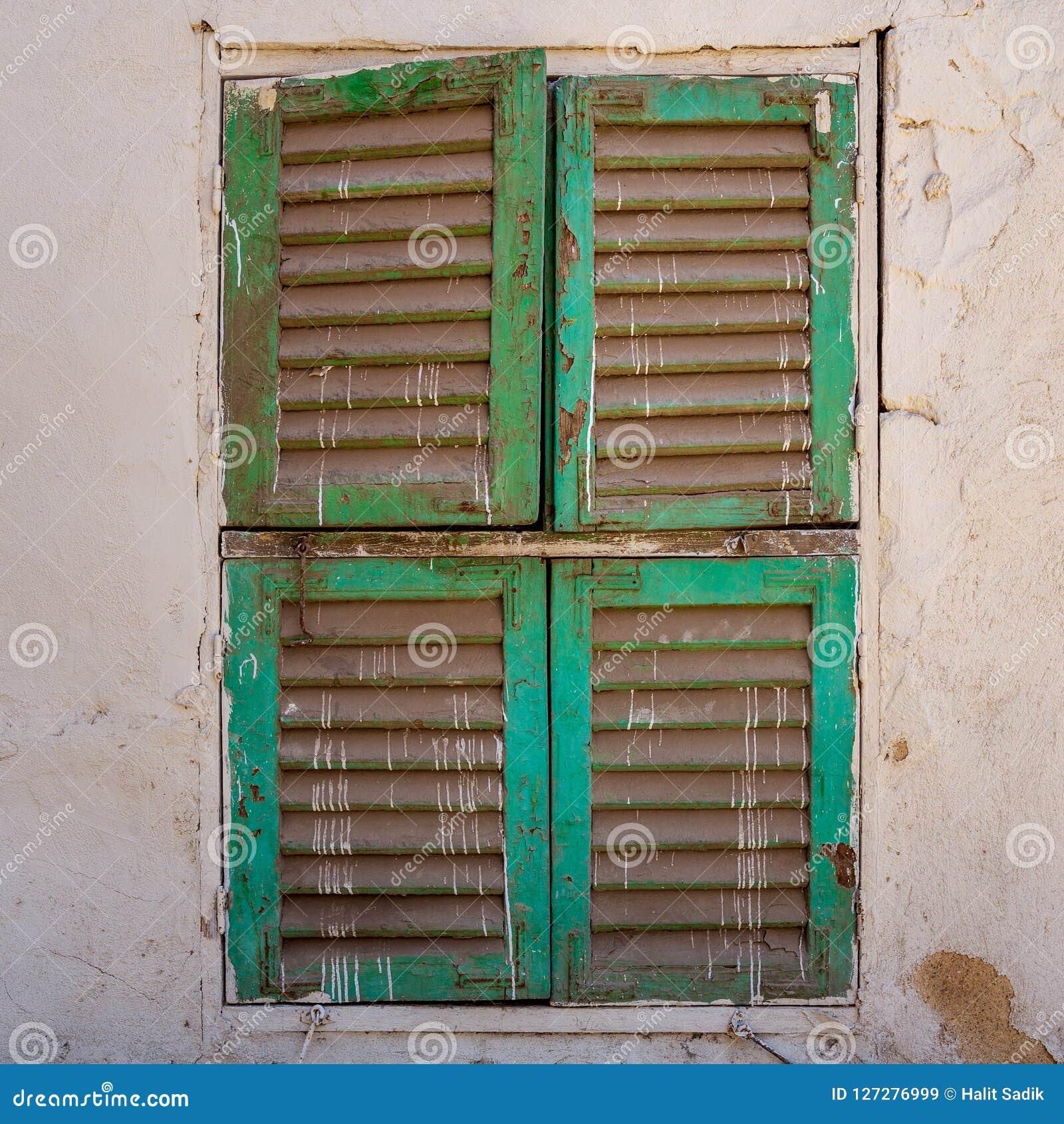 Oud grungevenster met gesloten groene blinden op de vuile muur van de bakstenensteen