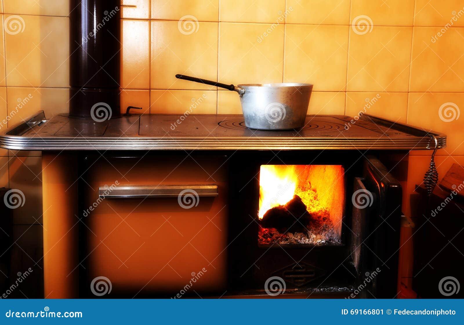 Oud houten brandt fornuis in de keuken van oud huis stock afbeelding