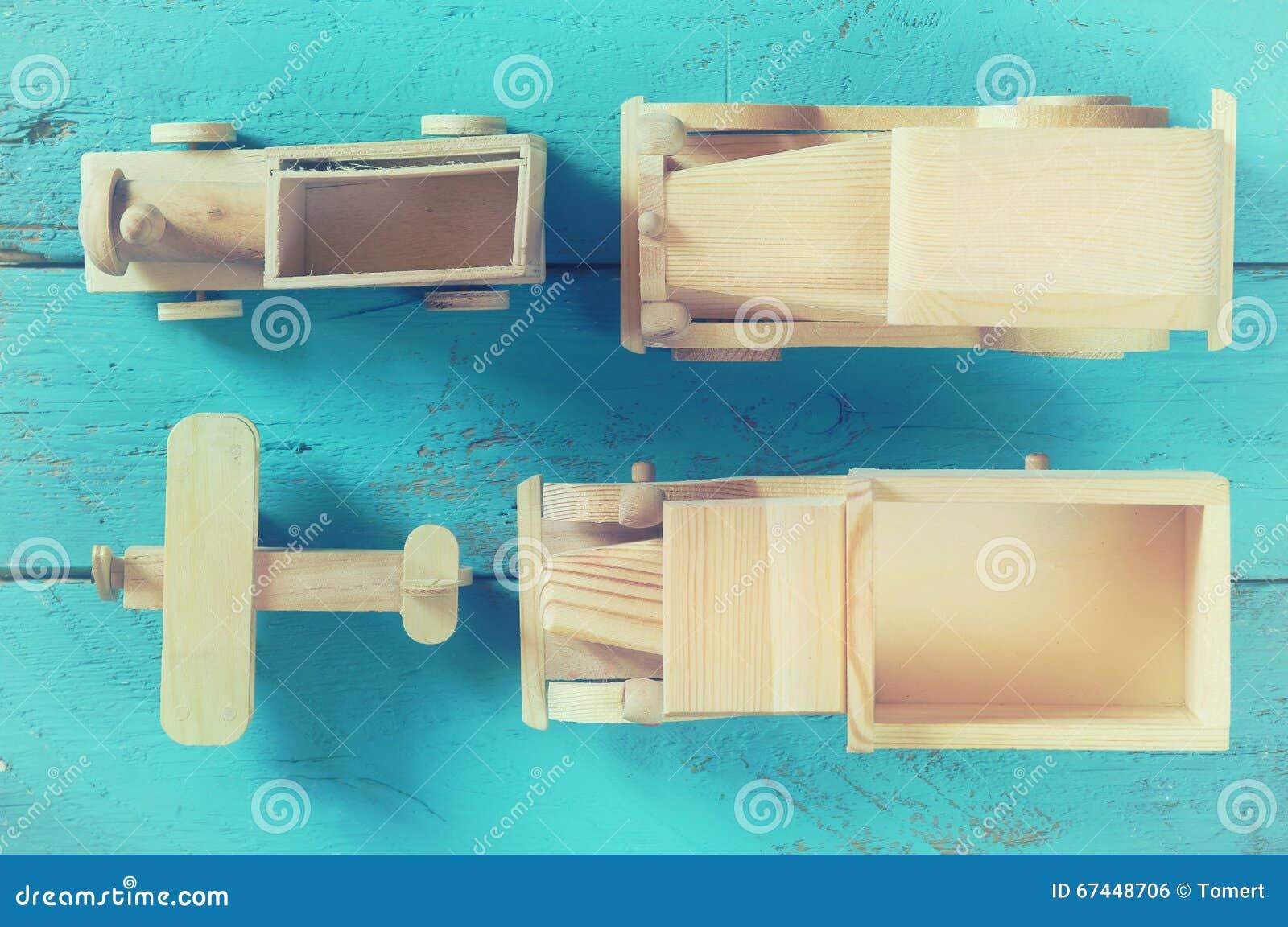 Oud houten vervoersspeelgoed: trein, auto, spoor en vliegtuig op blauwe houten achtergrond gefiltreerd en gestemde wijnoogst