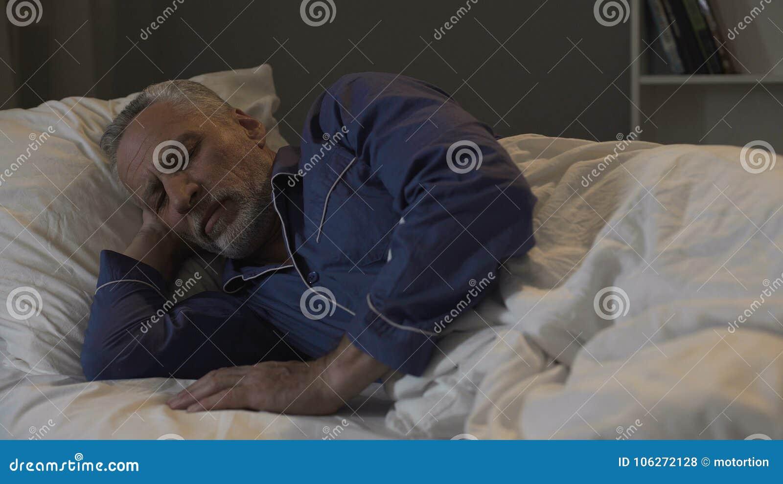 Oud mannetje die in zijn bed en slaap, terugwinningstijd en gezonde slaap, nacht liggen